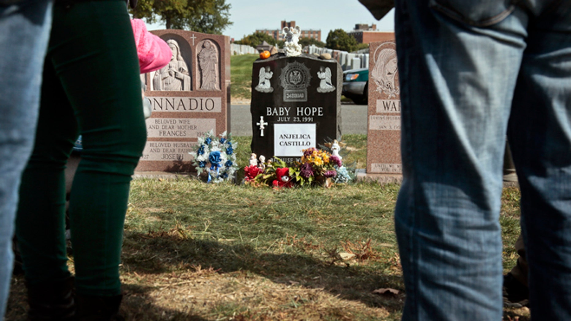 Visitors gather at the grave of Baby Hope, Anjelica Castillo, on Monday, Oct. 14, 2013 in the Bronx borough of New York.