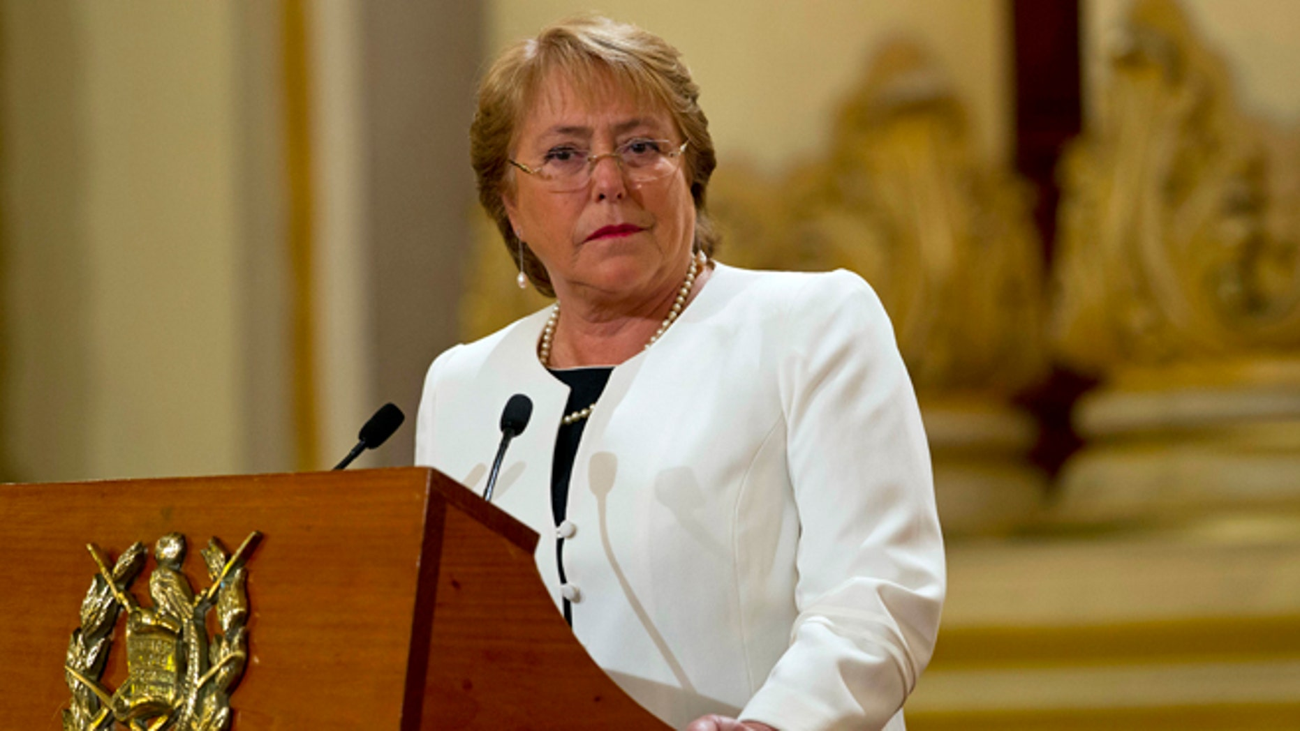 FILE - In this Friday, Jan. 30, 2015, file photo, Chile's President Michelle Bachelet listens to Guatemala's President Otto Perez Molina during their joint press conference at the National Palace in Guatemala City. President Bachelet has asked on Wednesday, May 6, 2015, for all her Cabinet ministers to submit their resignations. (AP Photo/Moises Castillo, File)