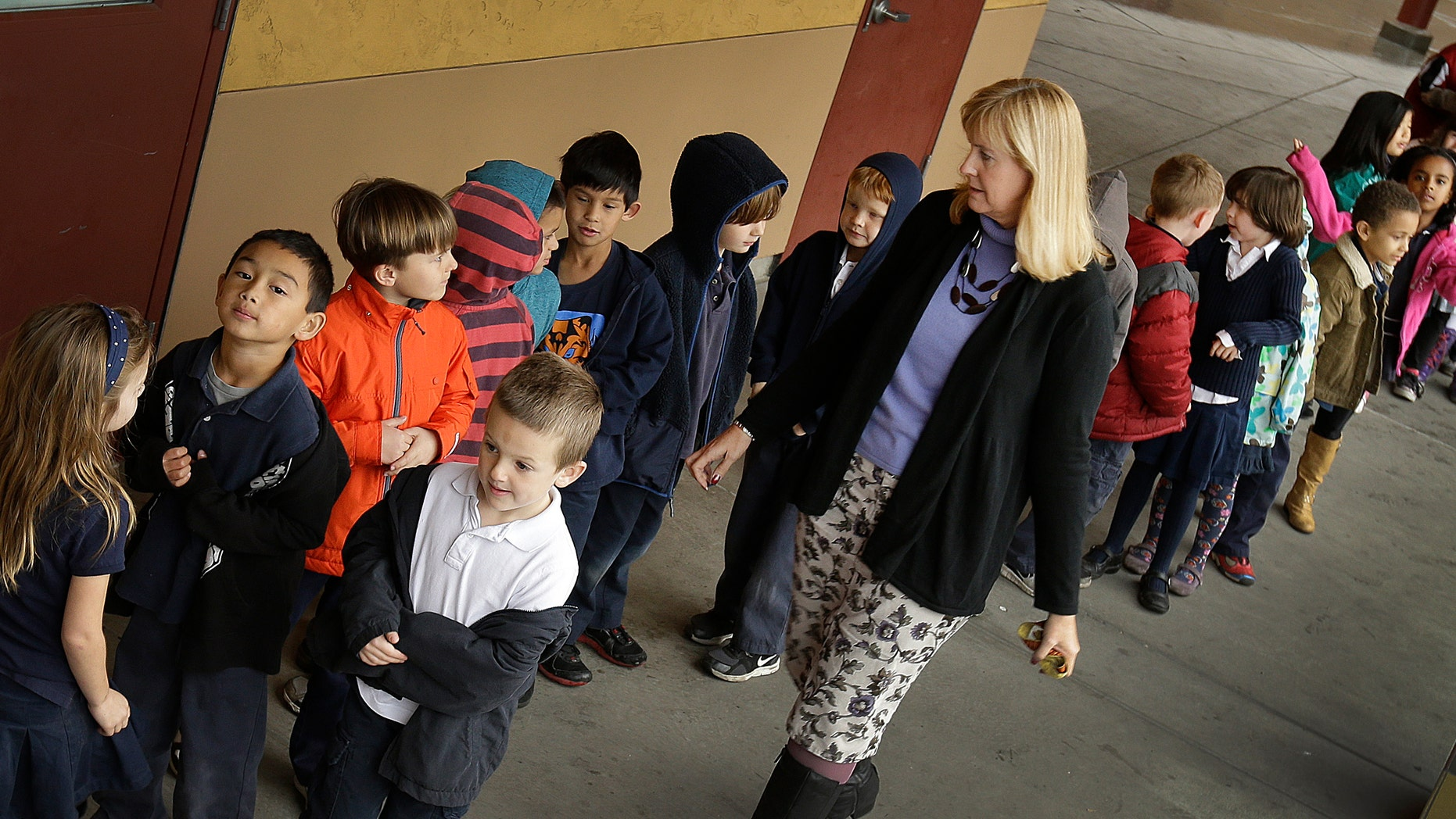 FILE - In this July 24, 2013 file photo, first grade teacher Lynda Jensen walks with her class of 30 children at Willow Glenn Elementary School in San Jose, Calif. Minority and low-income parents are more likely to see serious problems in their schools, from low expectations to bullying and out-of-date technology and textbooks, than those who are affluent or white, according to an Associated Press-NORC Center for Public Affairs Research Poll. The divisions fall along the familiar fault lines of income, education and race that drive so much of American life. (AP Photo/Ben Margot, File)