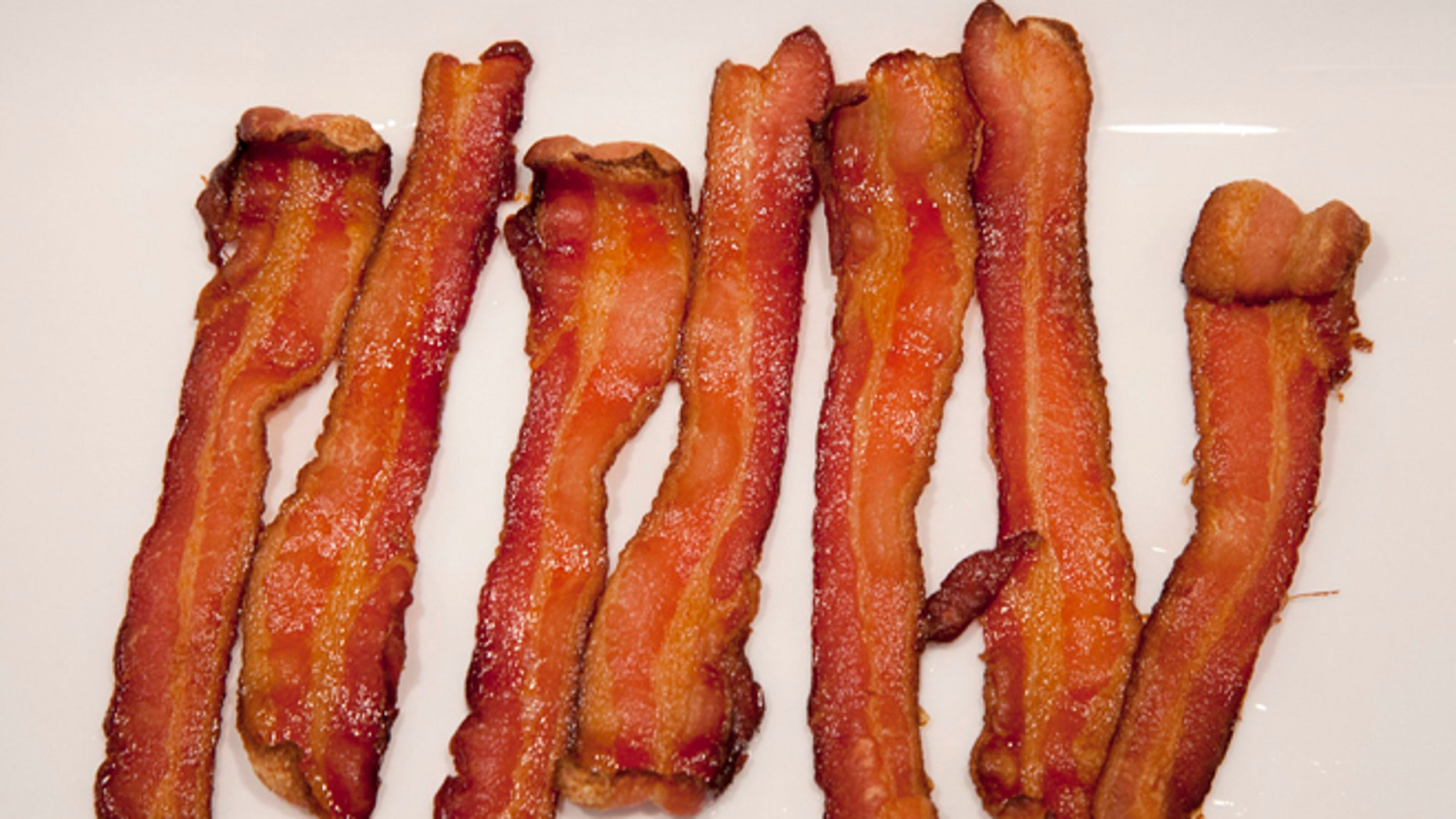 This Wednesday, Sept. 26, 2012 photo shows strips of cooked Bacon at a home in North Vancouver, British Columbia, Canada. A British farming organization is predicting a worldwide shortage of bacon and pork in 2013. The National Pig Association says global drought conditions are driving up the price of grain, a major staple in hog feed. It says pig farmers around the world are selling their herds because retail prices are not rising fast enough to cover the cost of record-high pig-feed costs. (The Canadian Press, Jonathan Hayward)