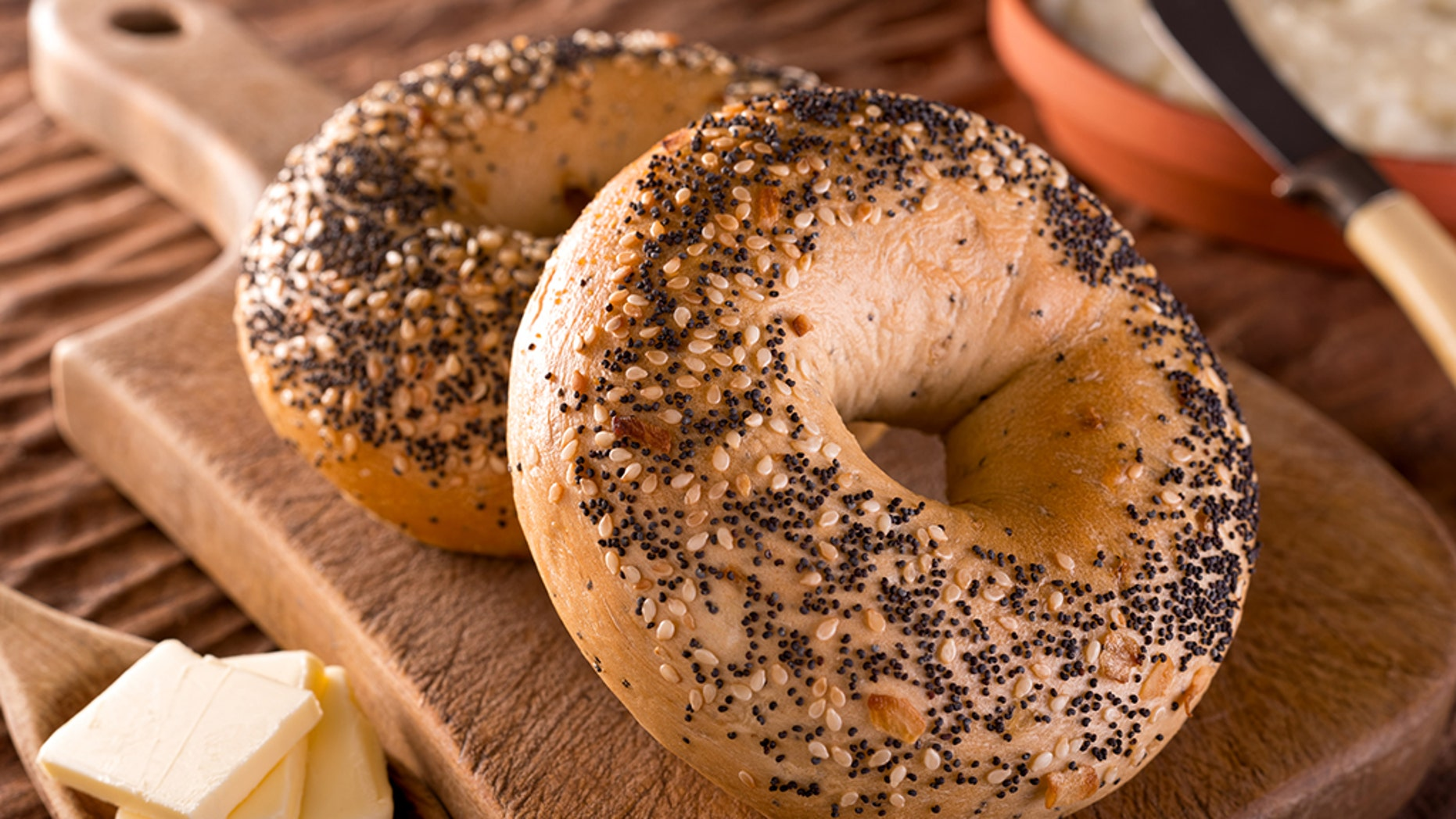 Freshly baked homemade bagels with onion, sesame seed, poppy seed, cream cheese, and butter.