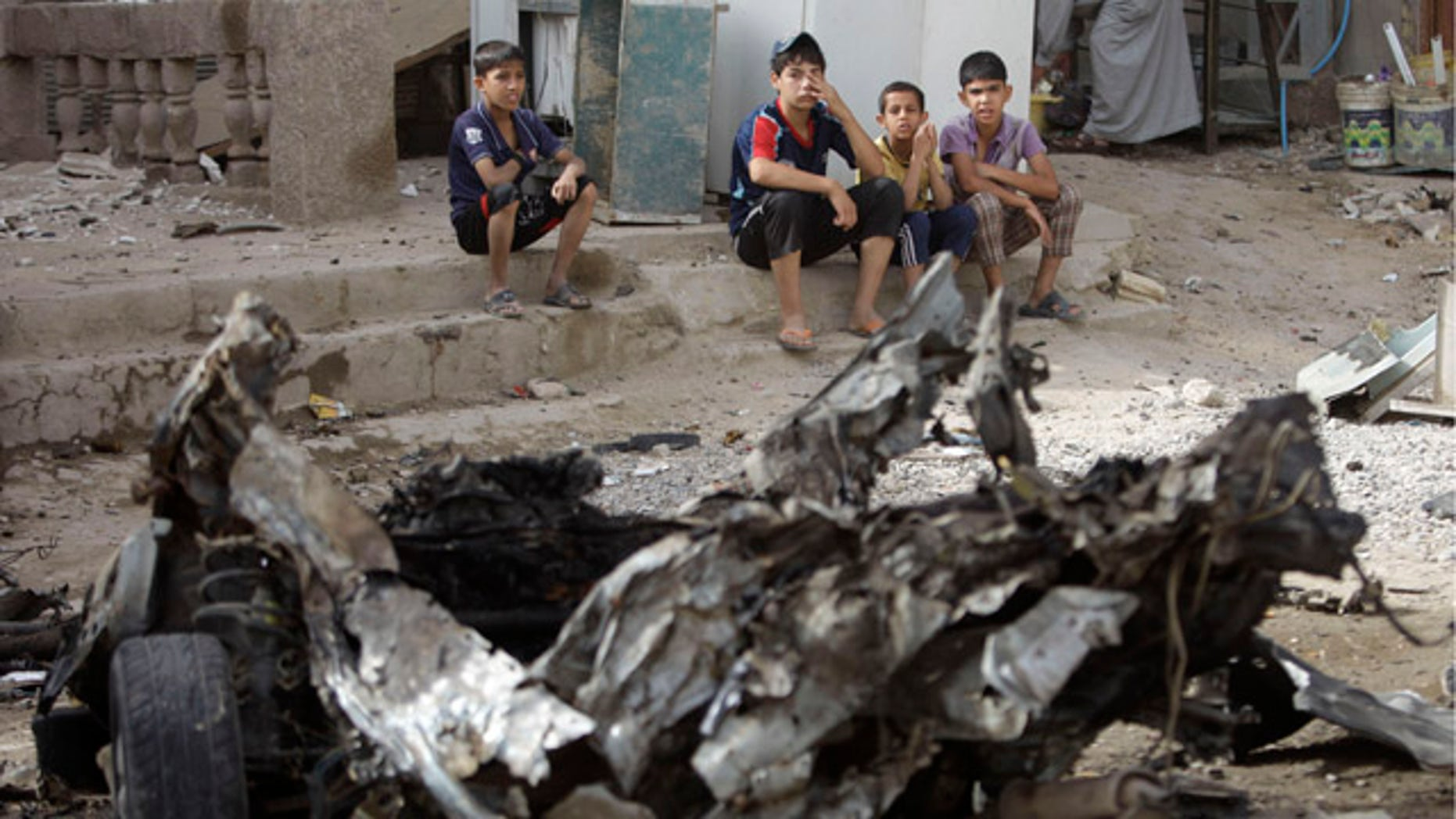 May 22: Boys sit near the scene of a car bomb attack in Baghdad, Iraq. A rapid-fire series of explosions in Baghdad while Iraqis were going to work on Sunday morning killed and wounded scores of people, police said
