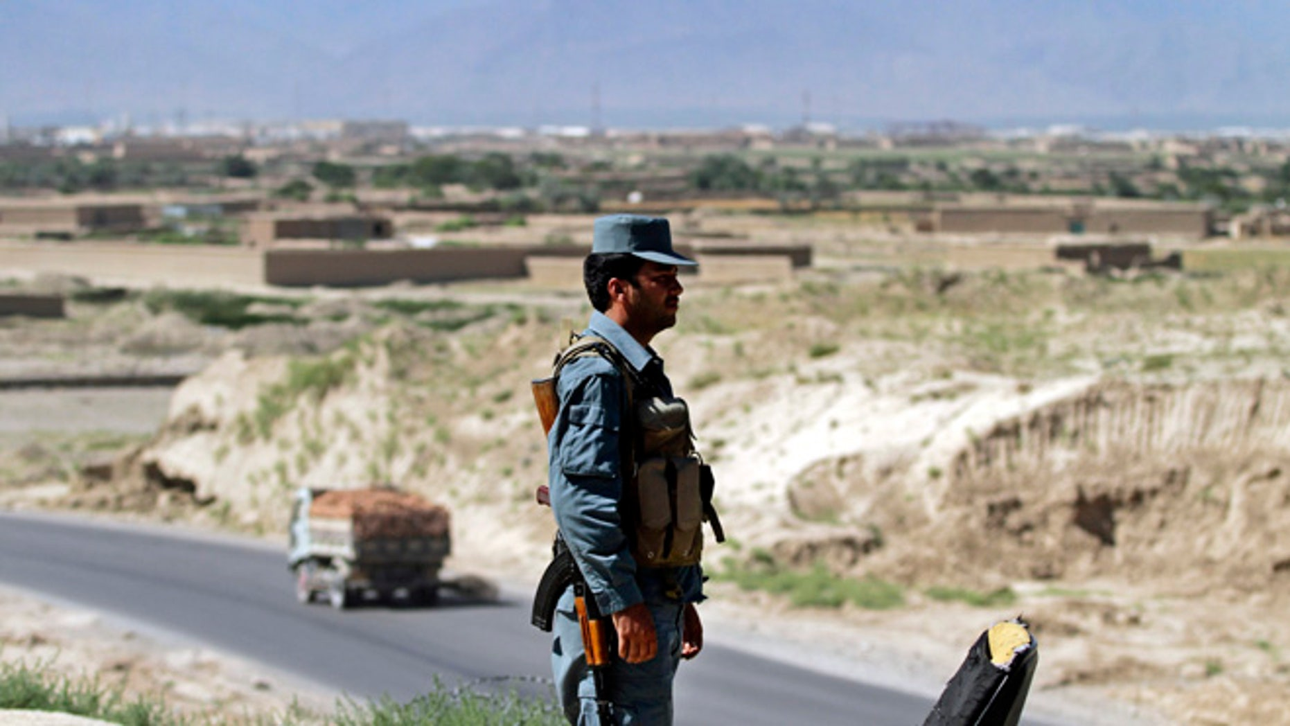 June, 19, 2013: An Afghan policeman stand guard outside Bagram military base, 31 miles north of Kabul, Afghanistan. The Taliban claimed responsibility Wednesday for an attack in Afghanistan that killed four American troops just hours after the insurgent group announced it would hold talks with the U.S. on finding a political solution to ending the nearly 12-year war in the country.