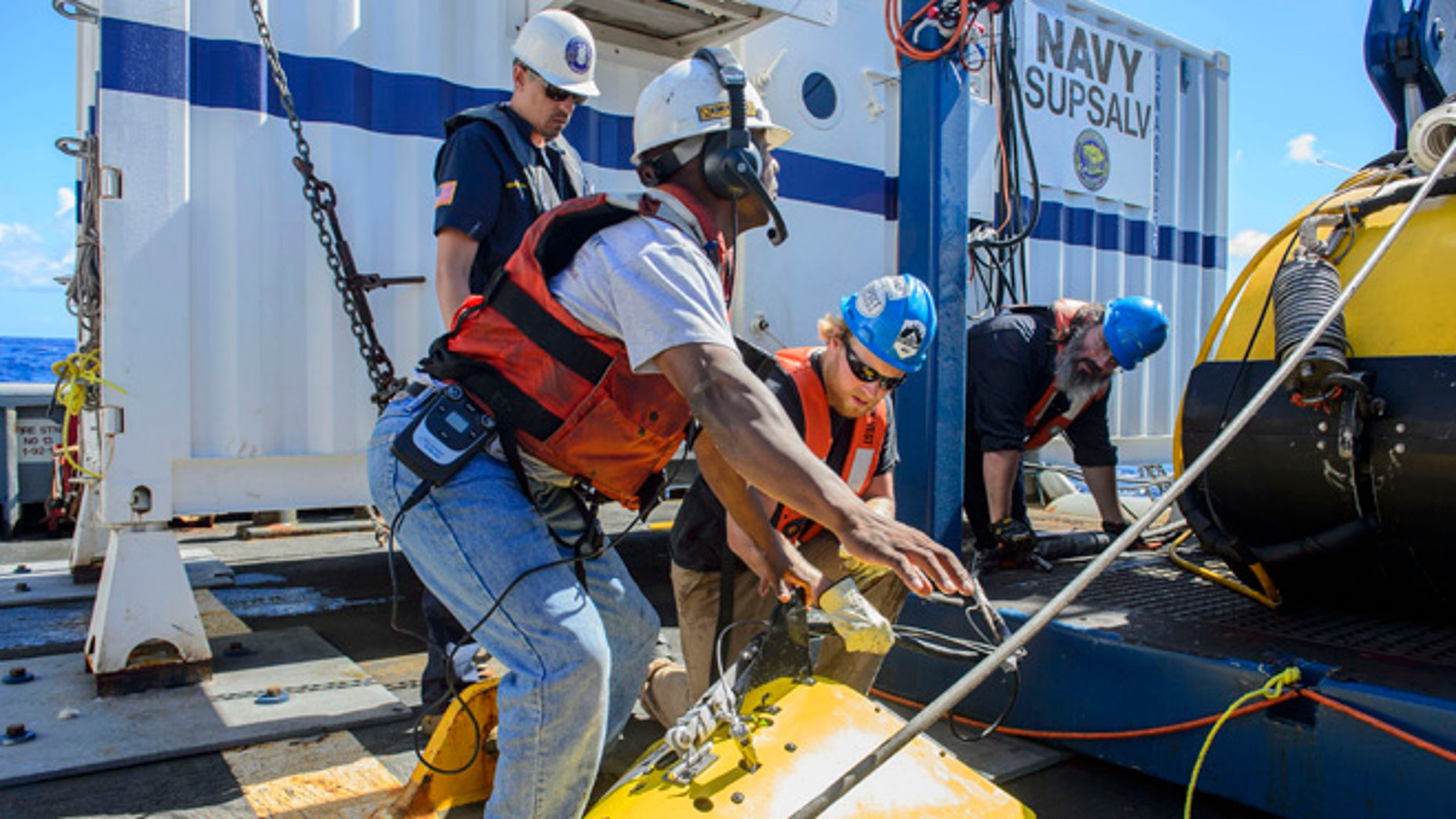 In this Oct. 24, 2015, photo, contractors and Lt. Cmdr. Daniel Neverosky retrieve and secure the tow pinger locater aboard the USNS Apache. USNS Apache departed Norfolk, Va., on Oct. 19, to begin searching for wreckage from the missing cargo ship El Faro. El Faro lost power and went down east of the Bahamas during Hurricane Joaquin. (John Paul Kotara II/Navy via AP)