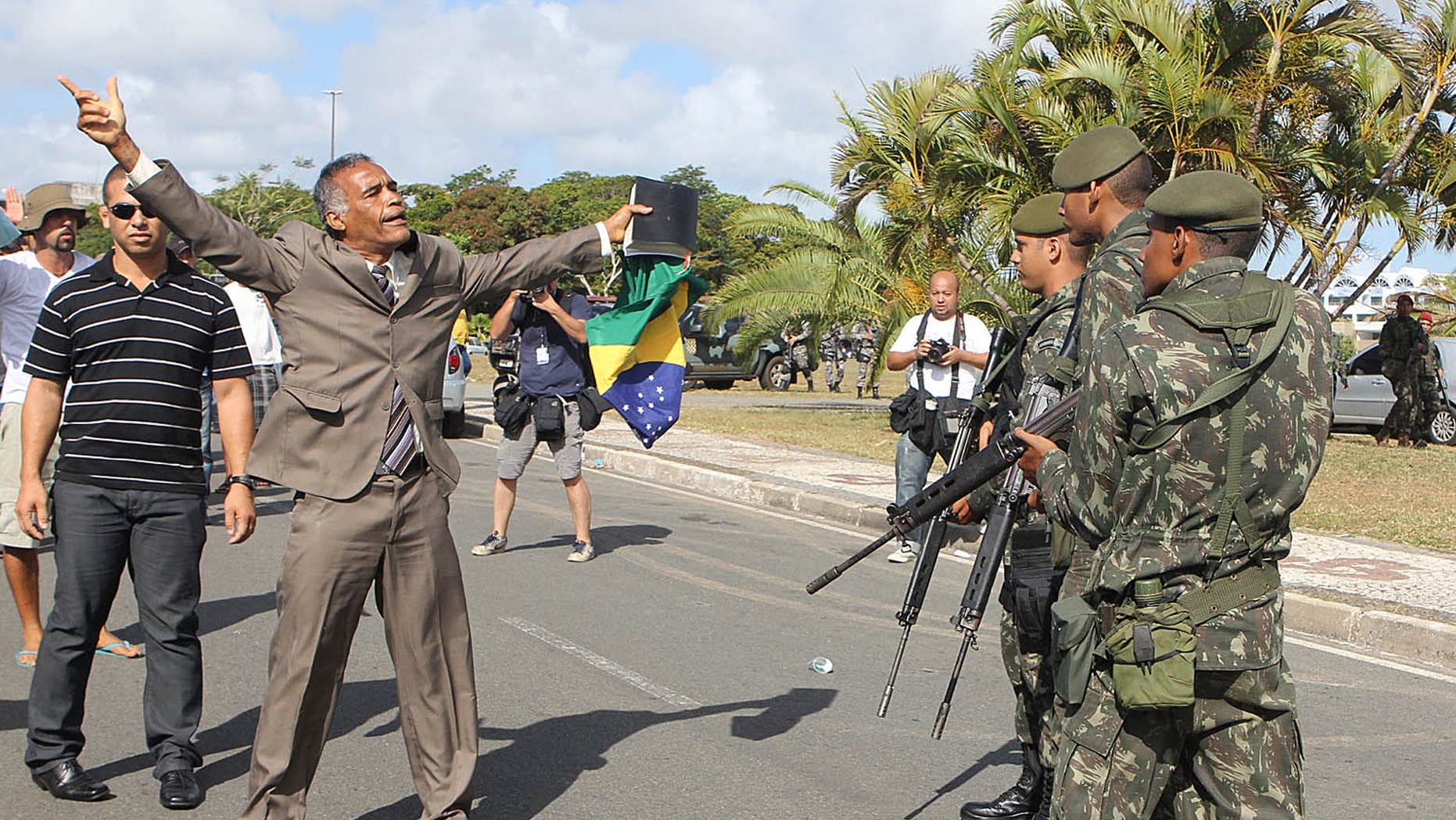 A protester shouts to soldiers during a police strike, in Salvador, Brazil, Monday, Feb. 6, 2012. Murder rates in Brazil's northeastern city of Salvador have more than doubled since the start of a police strike, media reports said Sunday. The strike has thrown a pall over preparations for Carnival in Brazil's third largest city, unleashing a rash of looting and a spike in the murder. (AP Photo/Paulo Macedo)
