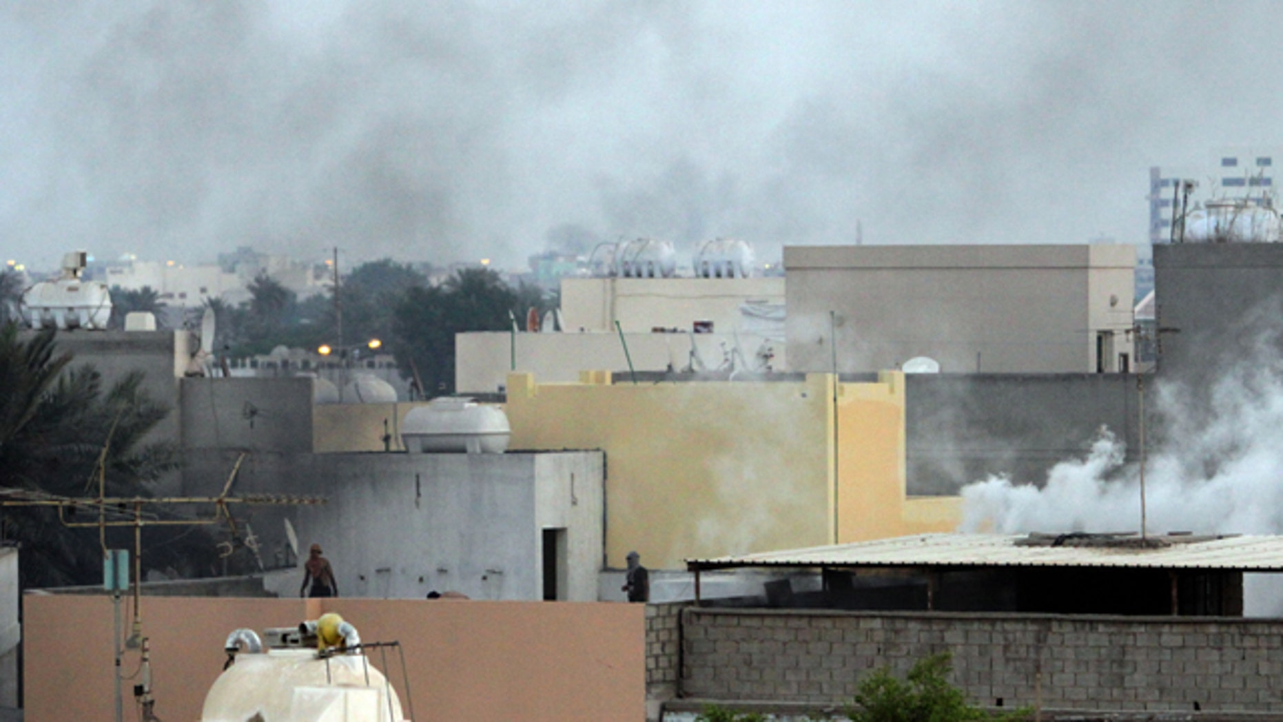 Sept. 24: Bahraini protesters move along rooftops as tear gas billows in the Shiite village of Sanabis, Bahrain, during a clash with riot police.
