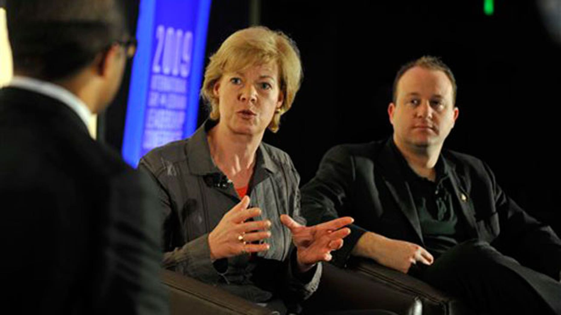 FILE: U.S. Rep. Tammy Baldwin, center, and U.S. Rep. Jared Polis, right, both openly gay members of Congress.