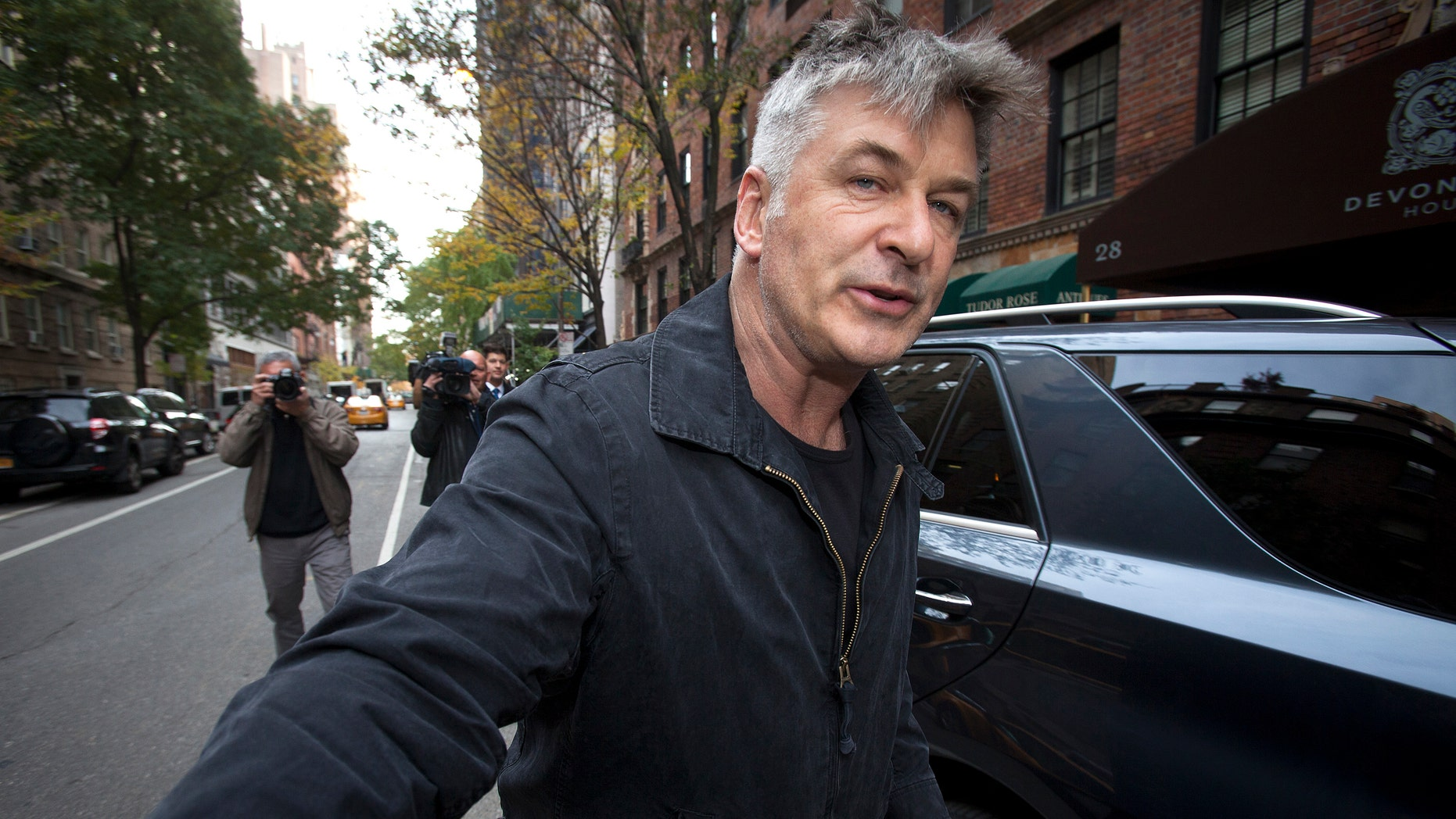 Actor Alec Baldwin shoves a photographer and tells him to move out of his way after he arrived in his SUV at the building where he lives in New York November 15, 2013. (REUTERS/Carlo Allegri)