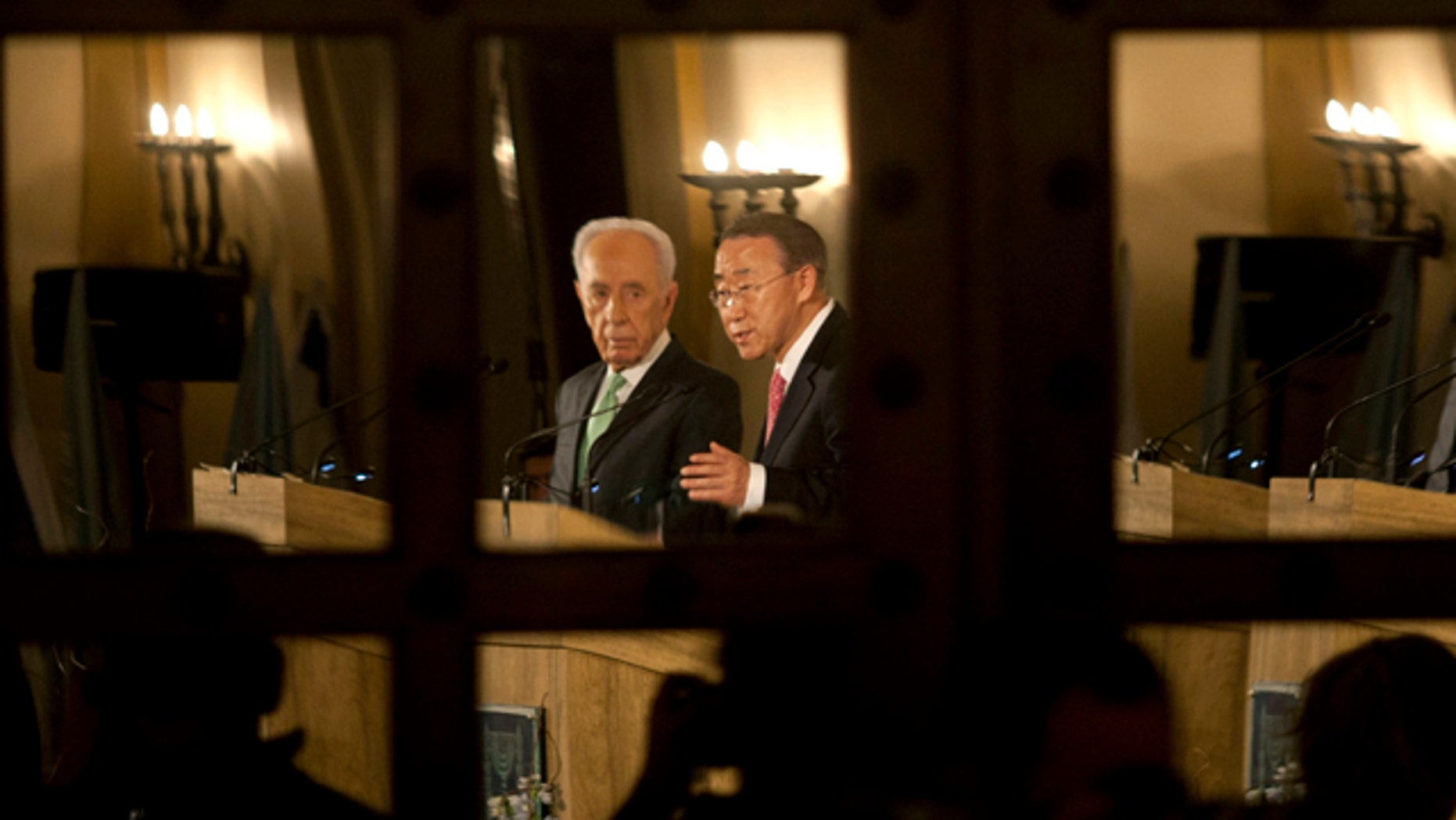 Feb. 1: Israel's President Shimon Peres, left, and United Nations Secretary General Ban Ki-moon are seen reflected in a door's mirror as they speak at a Jerusalem hotel.