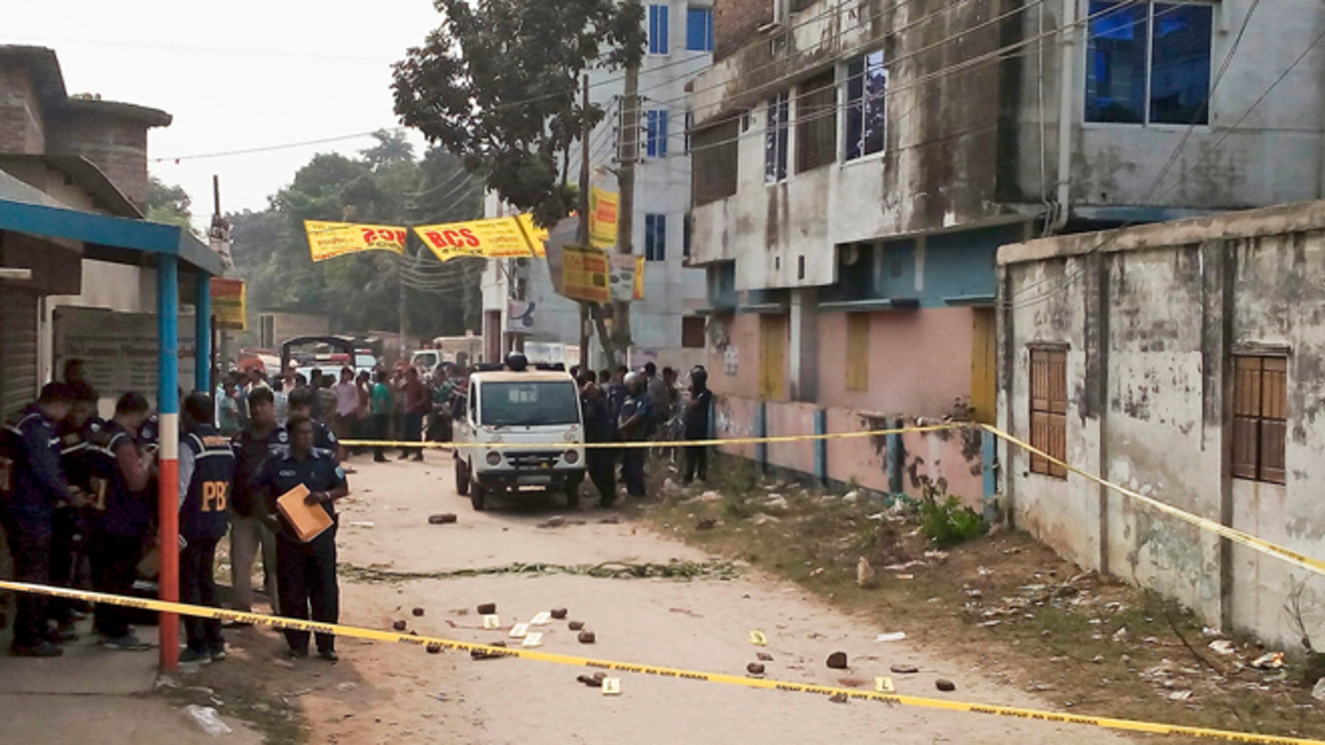 Nov. 18, 2015: Members of Bangladesh's Police Bureau of Investigation stand by the site where an Italian priest was attacked.