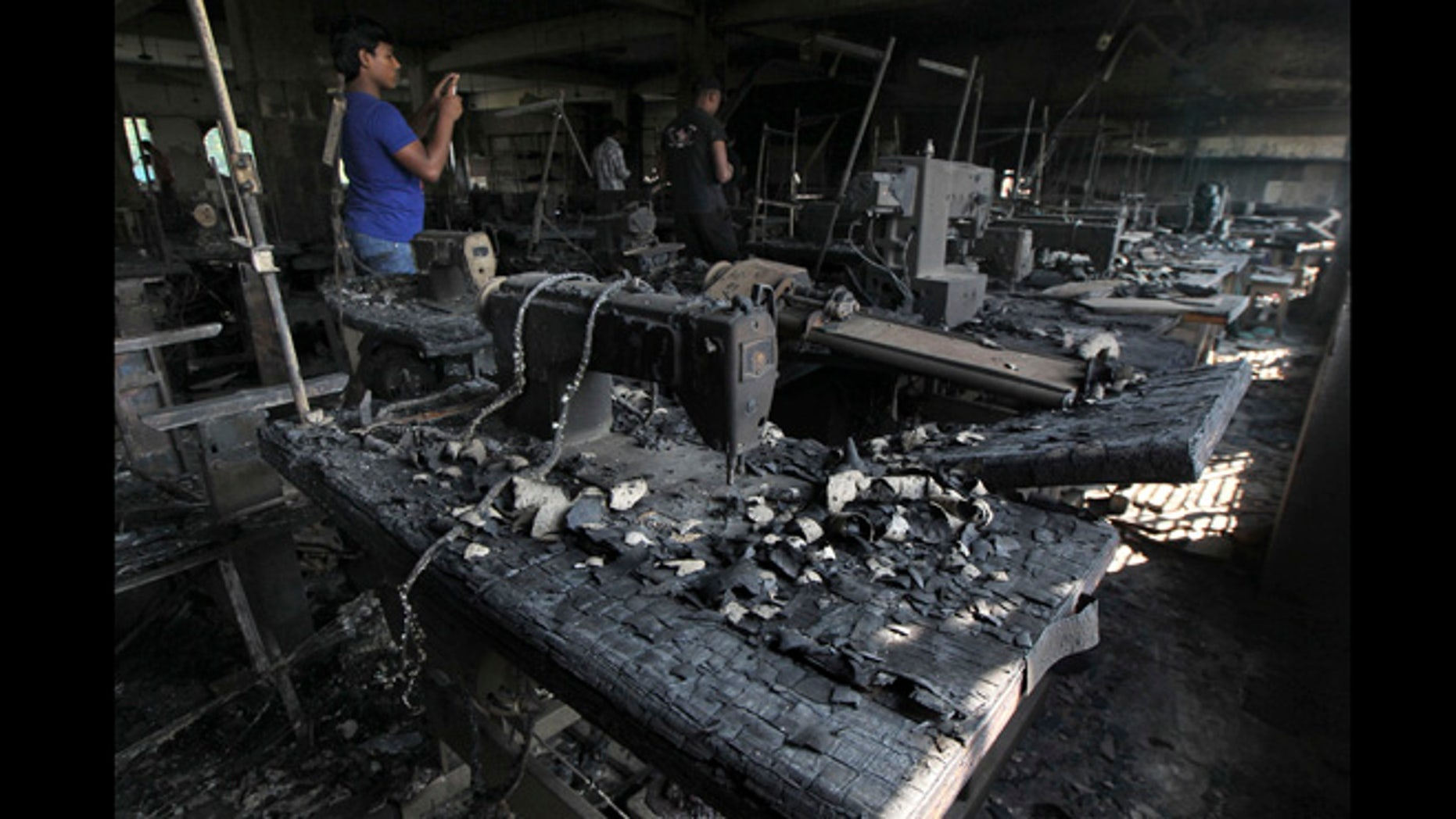 Nov. 26, 2012: A man takes photographs inside a garment-factory where a fire killed more than 110 people Saturday  on the outskirts of Dhaka, Bangladesh.