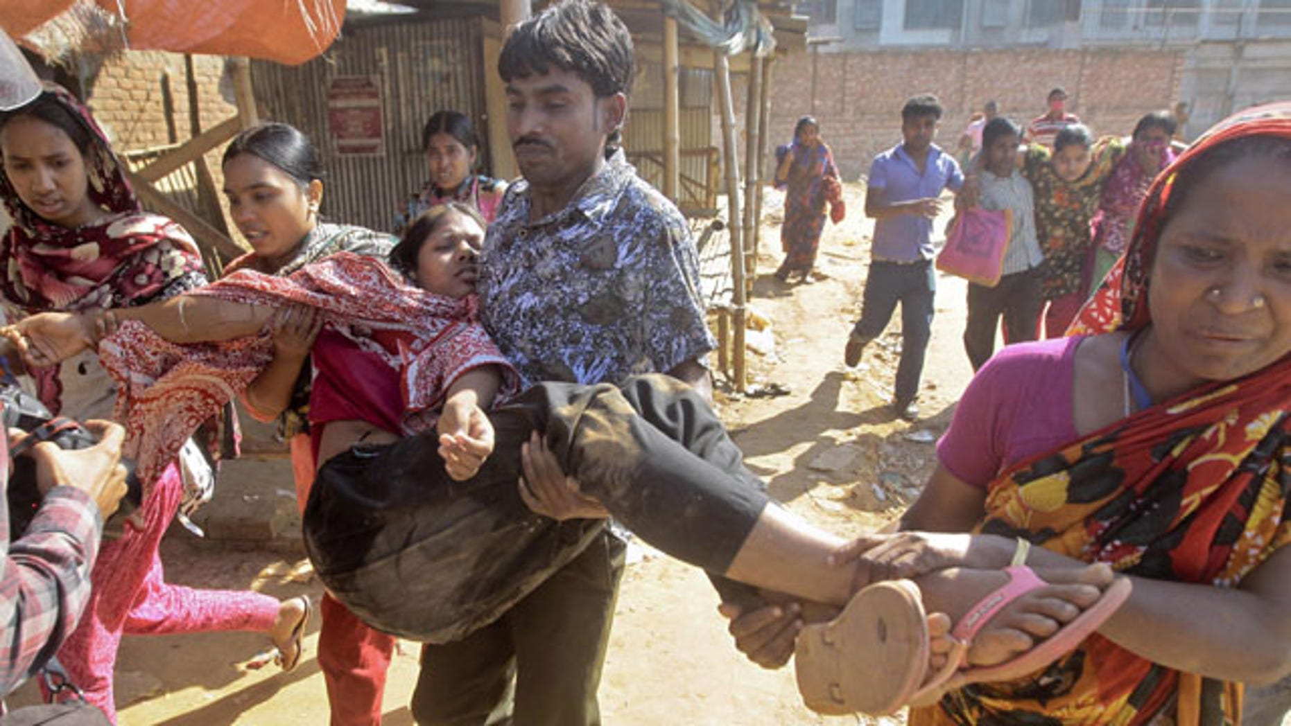 November 12, 2013: Bangladeshi garment workers assist their colleagues injured during a clash with police in Ashulia, outskirts of Dhaka, Bangladesh. Thousands of garment workers demanding higher pay clashed with police for a second day Tuesday, leaving dozens of people injured and at least 200 factories closed, police said. (AP Photo/A.M. Ahad)