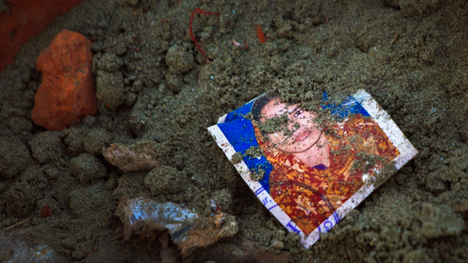 May 5: A photo of a missing garment worker is partially buried in soil at the site of the garment factory building collapse in Savar, near Dhaka, Bangladesh.