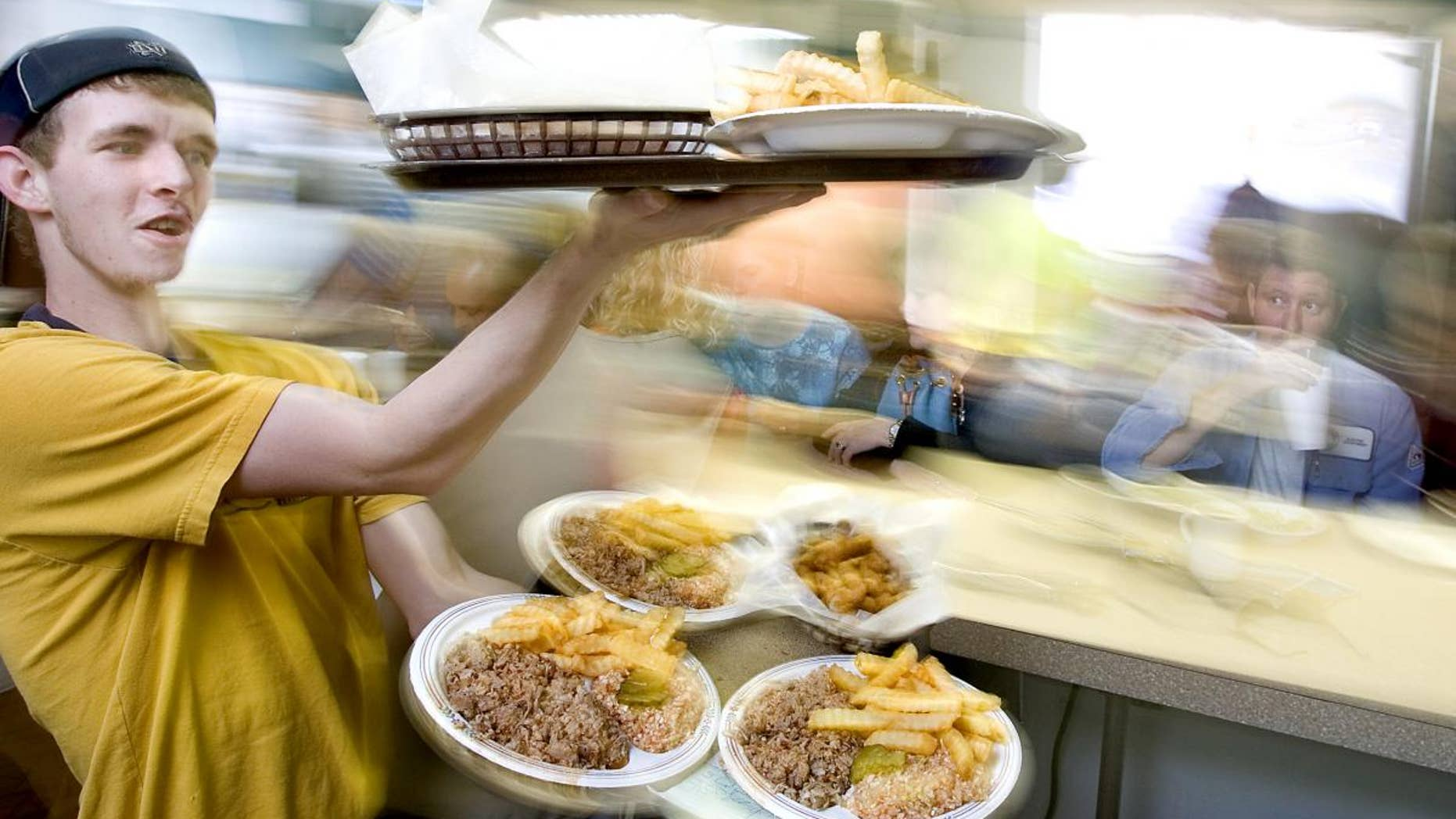 Matthew Hege carries trays of barbecue plates to customers at a barbecue restaurant in Lexington, North Carolina.  (AP File Photo/News-Record, H. Scott Hoffmann)