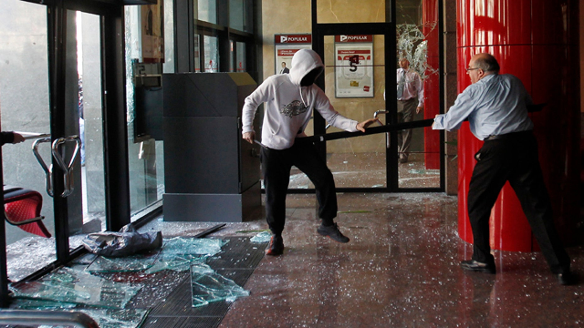 Feb. 29: A man confronts a hooded protester who was vandalising a bank during a protest against cuts in public education in Barcelona.