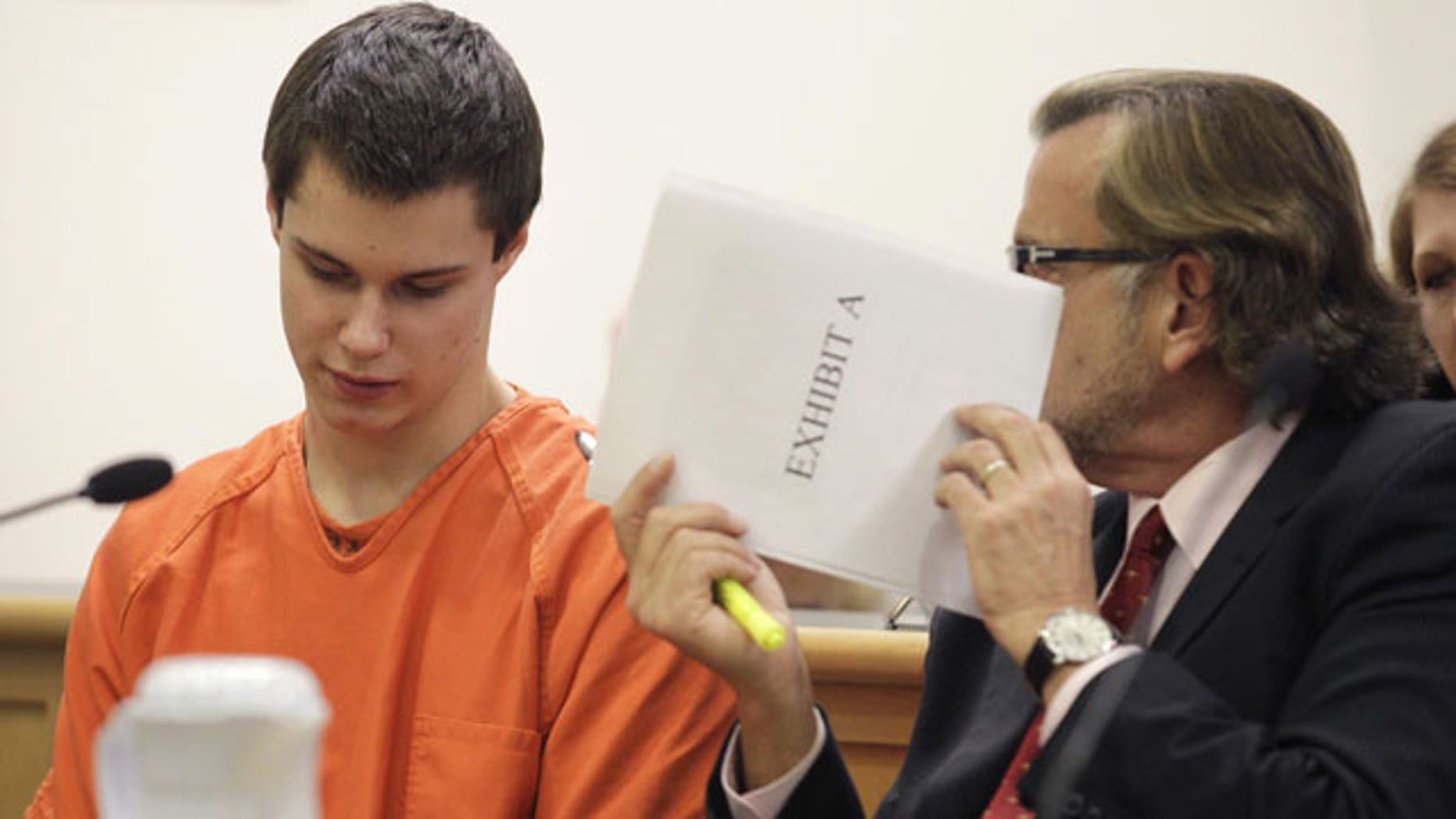 December 16, 2011: Attorney John Henry Browne, right, uses a court document to shield his conversation with Colton Harris-Moore, in Island County Superior Court in Coupeville, Wash. Harris-Moore was later sentenced to more than seven years in prison after pleading guilty to dozens of state charges stemming from a two-year crime spree.