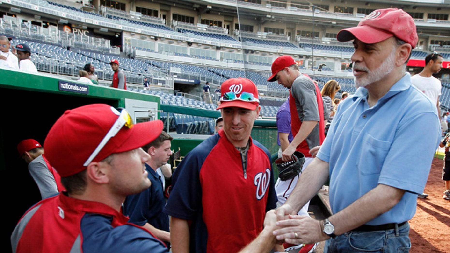 Washington Nationals third baseman Ryan Zimmerman, left, and first baseman Adam LaRoche, center, greeting Federal Reserve Board Chairman Ben Bernanke before a baseball game against the Miami Marlins at Nationals Park in Washington.