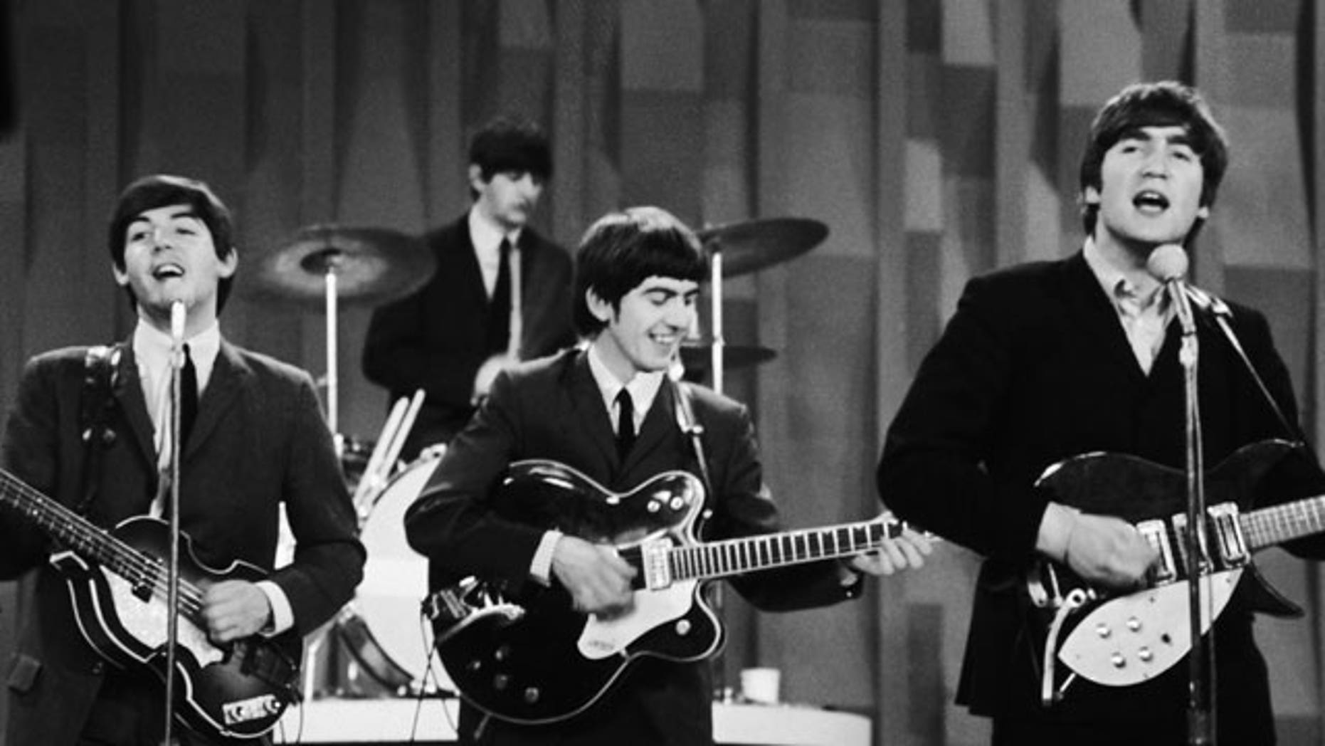 """In this Feb. 9, 1964 file photo, The Beatles  perform on the CBS """"Ed Sullivan Show"""" in New York. Ringo Starr plays drums, rear, and playing guitars from left are Paul McCartney, George Harrison and John Lennon."""