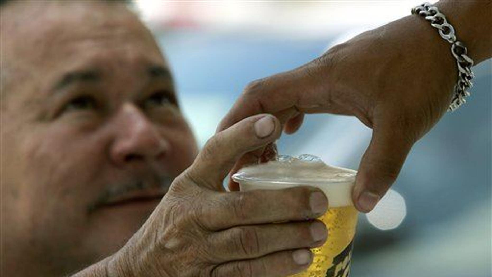 A man buys beer in an outdoor bar at Caracas's auto show, Sunday, Oct 7, 2007.  Venezuela's President Hugo Chavez is on a moral crusade, preaching against vices from alcohol to cholesterol, vowing to curb whisky imports and ordering beer trucks off the street.