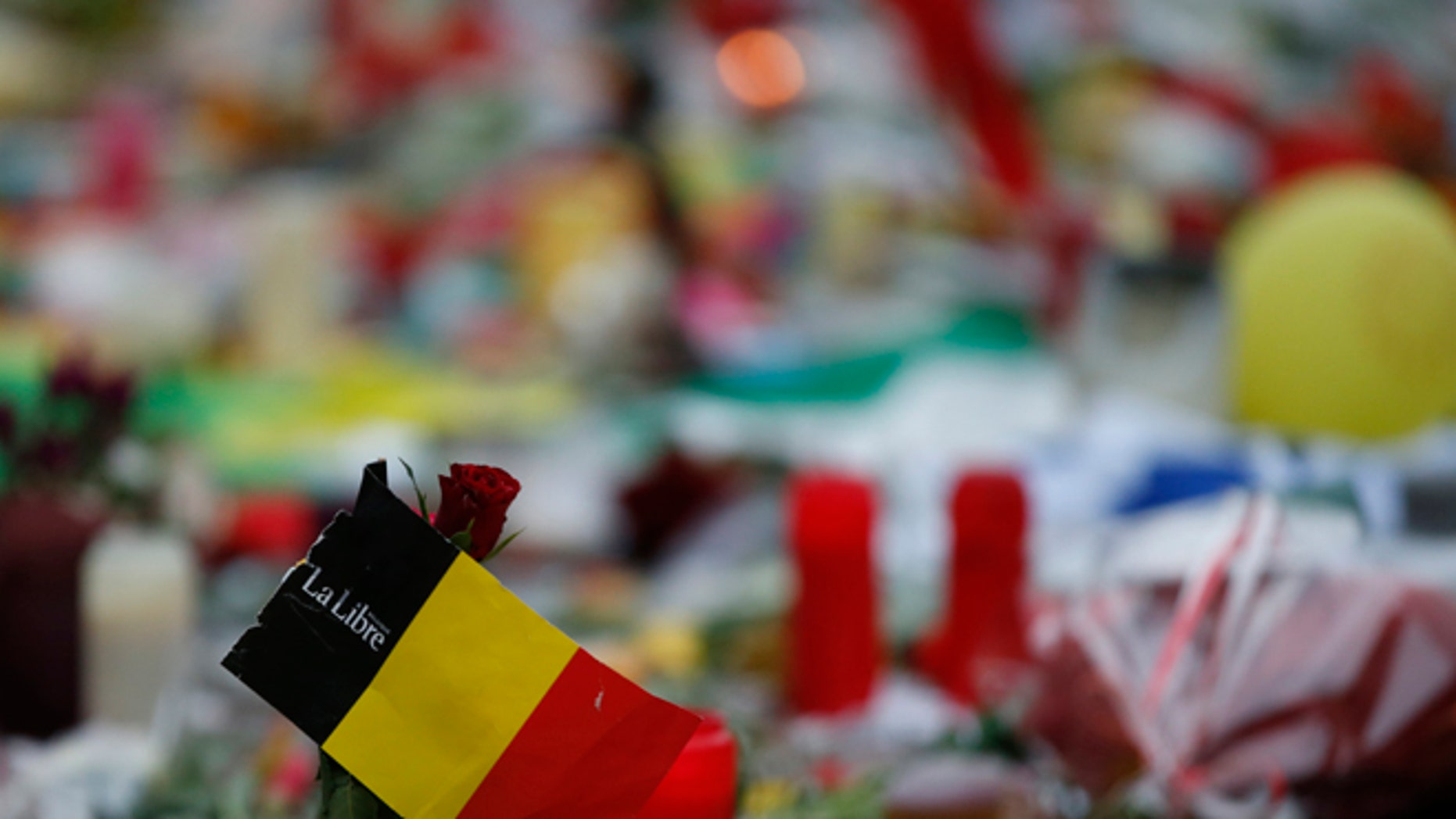 """A red rose and the national flag of Belgium amongst the tributes to the victims of the recent attacks in Brussels, placed in the Place de la Bourse in the centre of Brussels, Thursday, March, 24, 2016. Belgium's prime minister is promising to do everything to determine who was responsible for deadly attacks targeting the Brussels airport and subway system. Charles Michel, in a national mourning speech Thursday, said Tuesday's attacks on the European Union's capital targeted the """"liberty of daily life"""" and """"the liberty upon which the European project was built.""""(AP Photo/Alastair Grant)"""