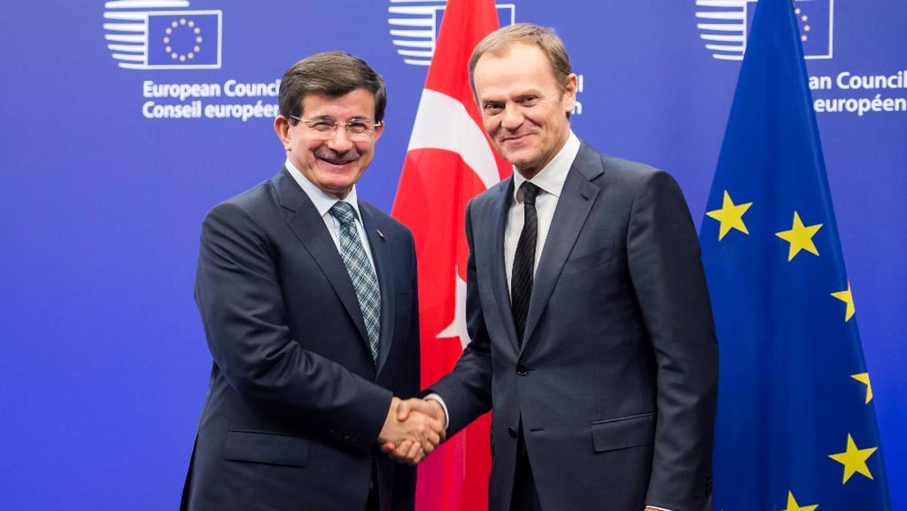 European Council President Donald Tusk, right, welcomes Turkey's Prime Minister Ahmet Davutoglu upon his arrival at the EU Council in Brussels on Thursday, Jan. 15, 2015. (AP Photo/Geert Vanden Wijngaert)