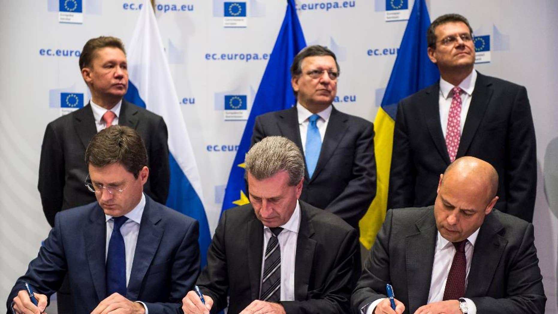 EU Commissioner for Energy Guenther Oettinger, center, Russian Energy Minister Alexander Novak , left, and Ukrainian Energy Minister Yuriy Prodan sign an agreement that guarantees Russian gas will continue to flow to Ukraine and, by extension, parts of the EU this winter as EU Commission President Jose Manuel Barroso, center back, Gazprom CEO Alexey Miller, left back and EU Commissioner for Inter-Institutional Relations and Administration Maros Sefcovic look on, at the European Commission headquarters in Brussels, Thursday, Oct. 30, 2014. (AP Photo/Geert Vanden Wijngaert)