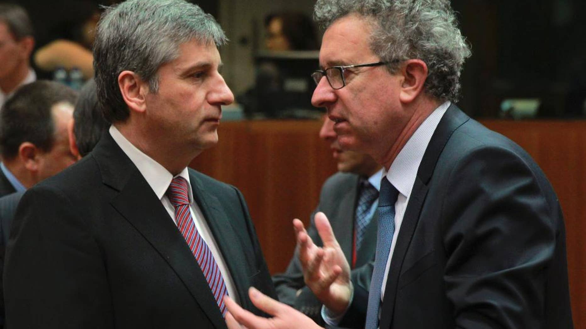 Austrian Finance Minister Michael Spindelegger, left, talks with his Luxembourg's counterpart Pierre Gramegna at the start of an EU finance ministers meeting at the European Council building in Brussels, Tuesday, March 11, 2014. The Council prepares the presidency's mandate to finalize negotiations with the European Parliament on the proposal for a single resolution mechanism for banks. (AP Photo/Yves Logghe)