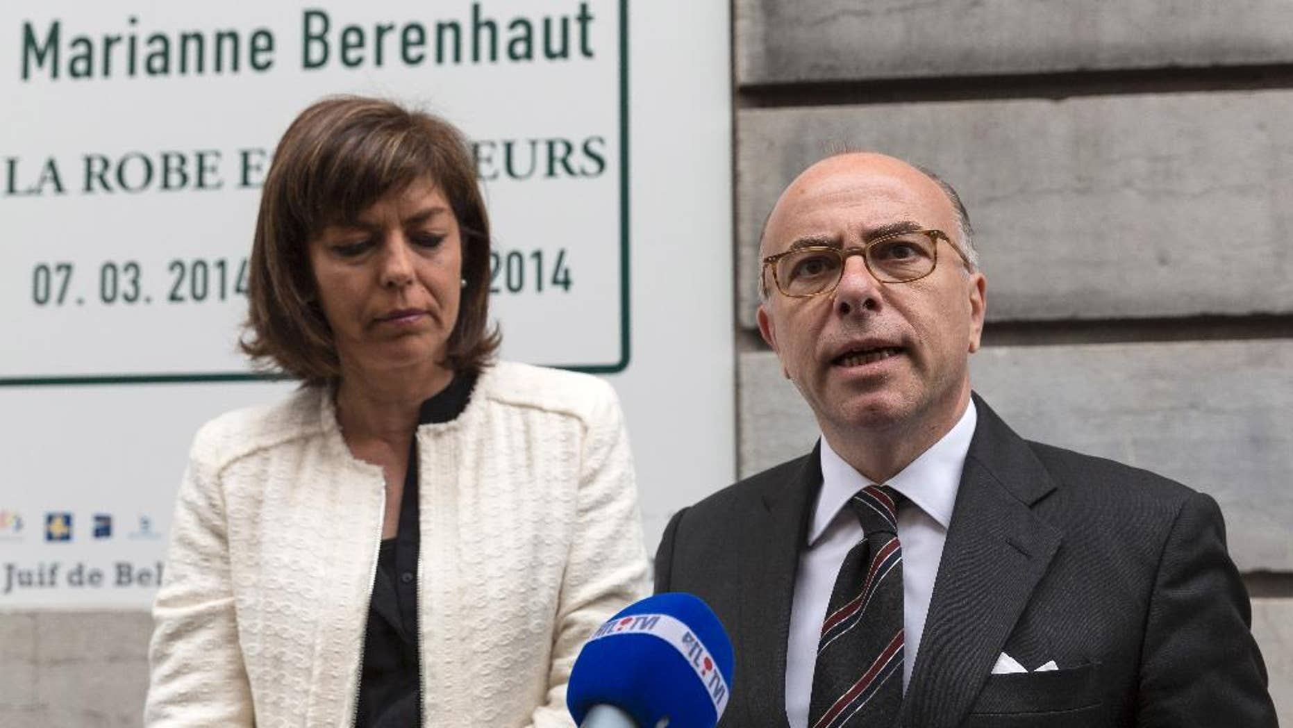 FILE - In this June 4, 2014 file photo, French Interior Minister Bernard Cazeneuve, right, and Belgium's Interior Minister Joelle Milquet speak with the press after laying a wreath at the Jewish Museum in Brussels on Wednesday, June 4, 2014. Recruiters for Islamic extremist groups are increasingly targeting French women and girls, with nearly 100 either in Syria or on their way and 175 being monitored at home, security officials say. France's Interior Ministry on Tuesday Sept.16, 2014 posted a video showing anguished family members of young people who left to fight alongside extremists, including a young man whose 15-year-old sister set out for what she thought was a humanitarian aid mission. She has not returned.  (AP Photo/Thierry Monasse, File)
