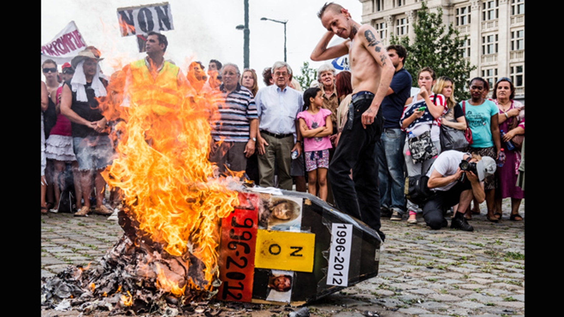 Aug. 19, 2012: Demonstrators gather around a burning mock coffin with the pictures of  Belgium's child killer Marc Dutroux and his ex-wife Michelle Martin during a march to remember their victims, in Brussels.