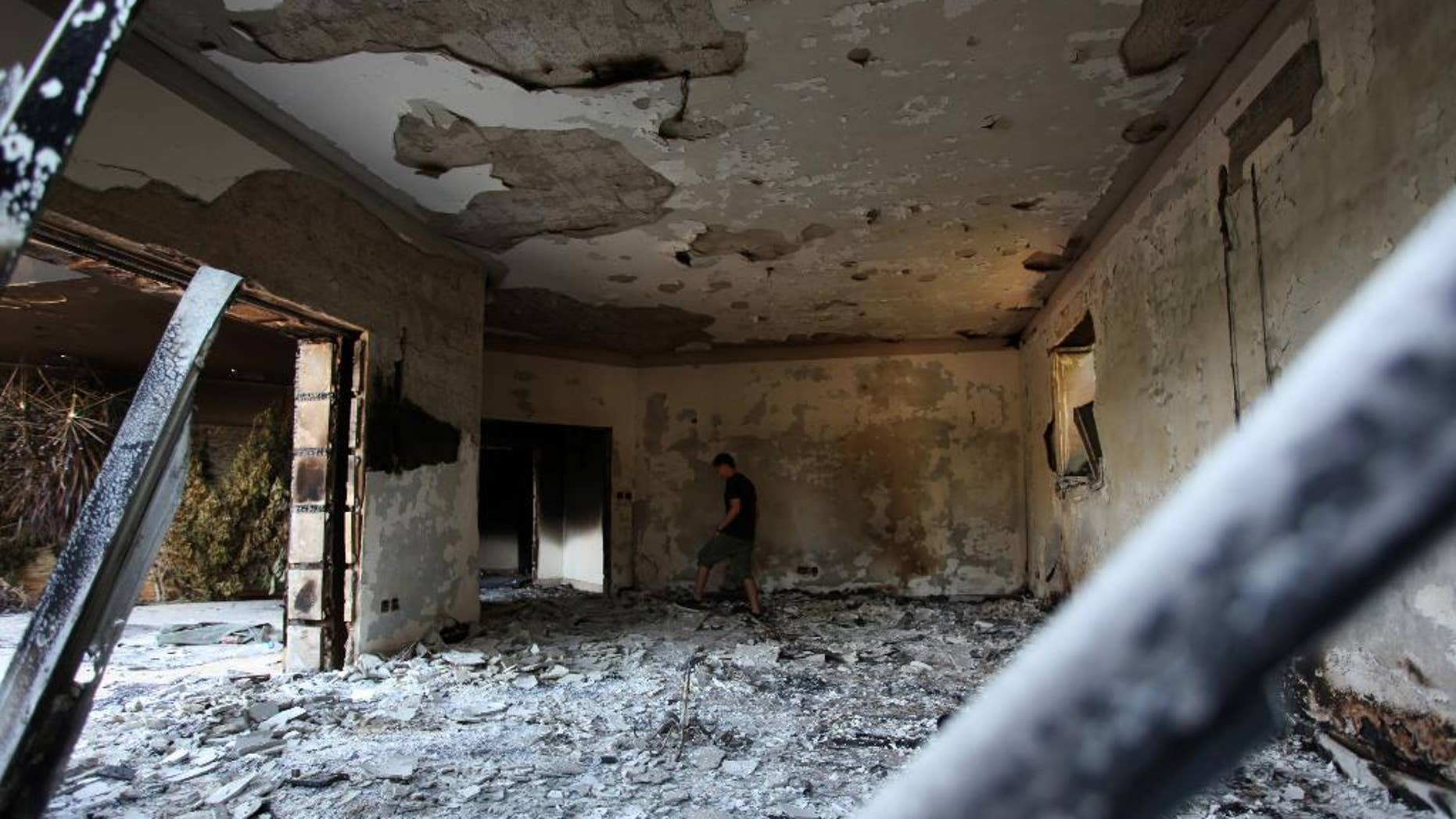 """FILE - This Sept. 13, 2012 file photo shows a Libyan man walking in the rubble of the damaged  U.S. consulate, after an attack that killed four Americans, including Ambassador Chris Stevens on the night of Tuesday, Sept. 11, 2012, in Benghazi, Libya. To congressional Republicans, """"Benghazi"""" is shorthand for incompetence and cover-up. Democrats hear it as the hollow sound of pointless investigations. It is, in fact, a Mediterranean port city in Libya that was the site of an attack on an American diplomatic compound on the 11th anniversary of 9/11 that killed U.S. Ambassador Chris Stevens and three other Americans. That's nearly all that U.S. politicians can agree on about Benghazi. (AP Photo/Mohammad Hannon, File)"""