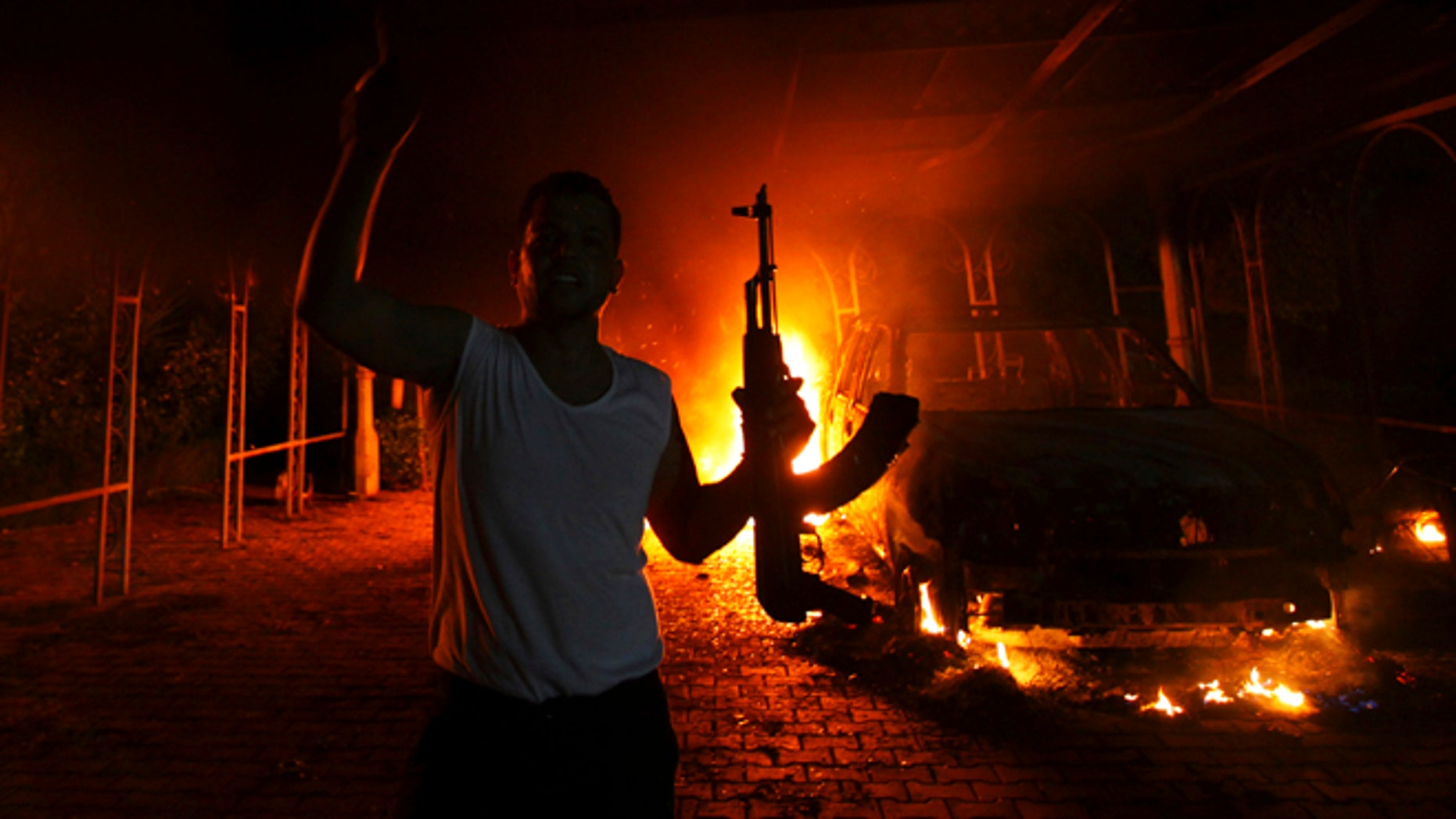 FILE 2012: A protester reacts as the U.S. Consulate in Benghazi is seen in flames. Sixty-six percent of voters want Congress to keep investigating the White House's handling of Benghazi, according to a Fox News poll.