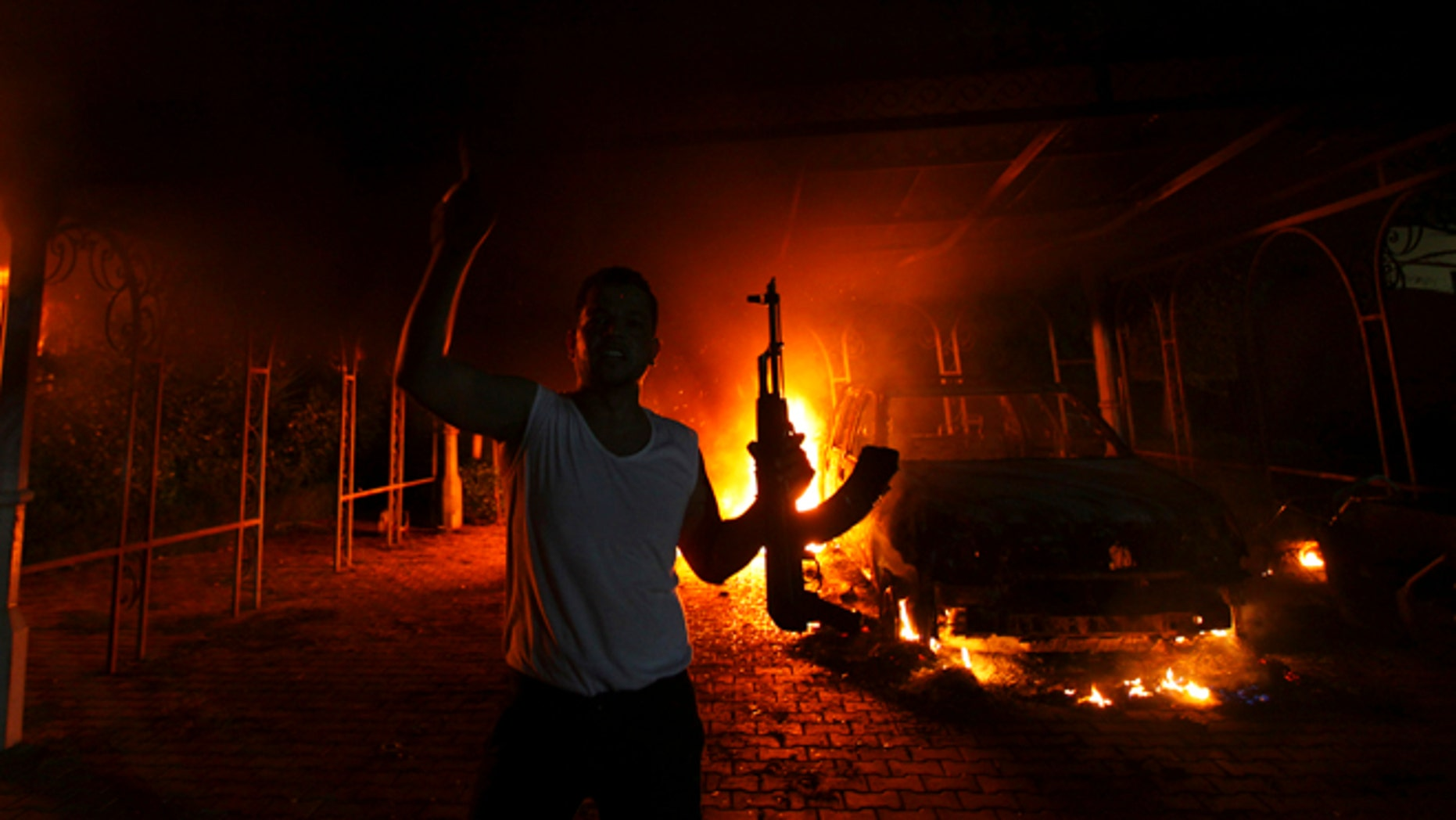 Sept. 11, 2012: A protester reacts as the U.S. Consulate in Benghazi is seen in flames during a protest by an armed group. (Reuters)