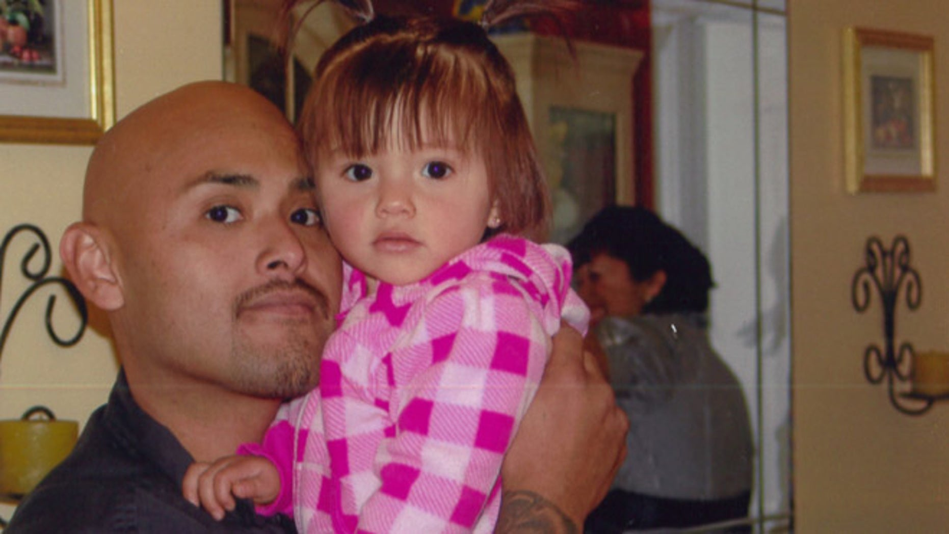 This undated photo provided by Galipo Law shows Benny Herrera holding his daughter, Abygail. A federal appeals court says a dashboard video shows a California police officer shooting and killing a man less than a second after ordering him to show his hands. The court noted the video footage Friday, Sept. 16, 2016, in rejecting Tustin Police Officer Osvaldo Villareal's request to dismiss the wrongful death lawsuit against him. The 9th U.S. Circuit Court of Appeals in San Francisco said Villareal couldn't have reasonably feared for his safety when he shot Herrera in December, 2011. (Galipo Law via AP)