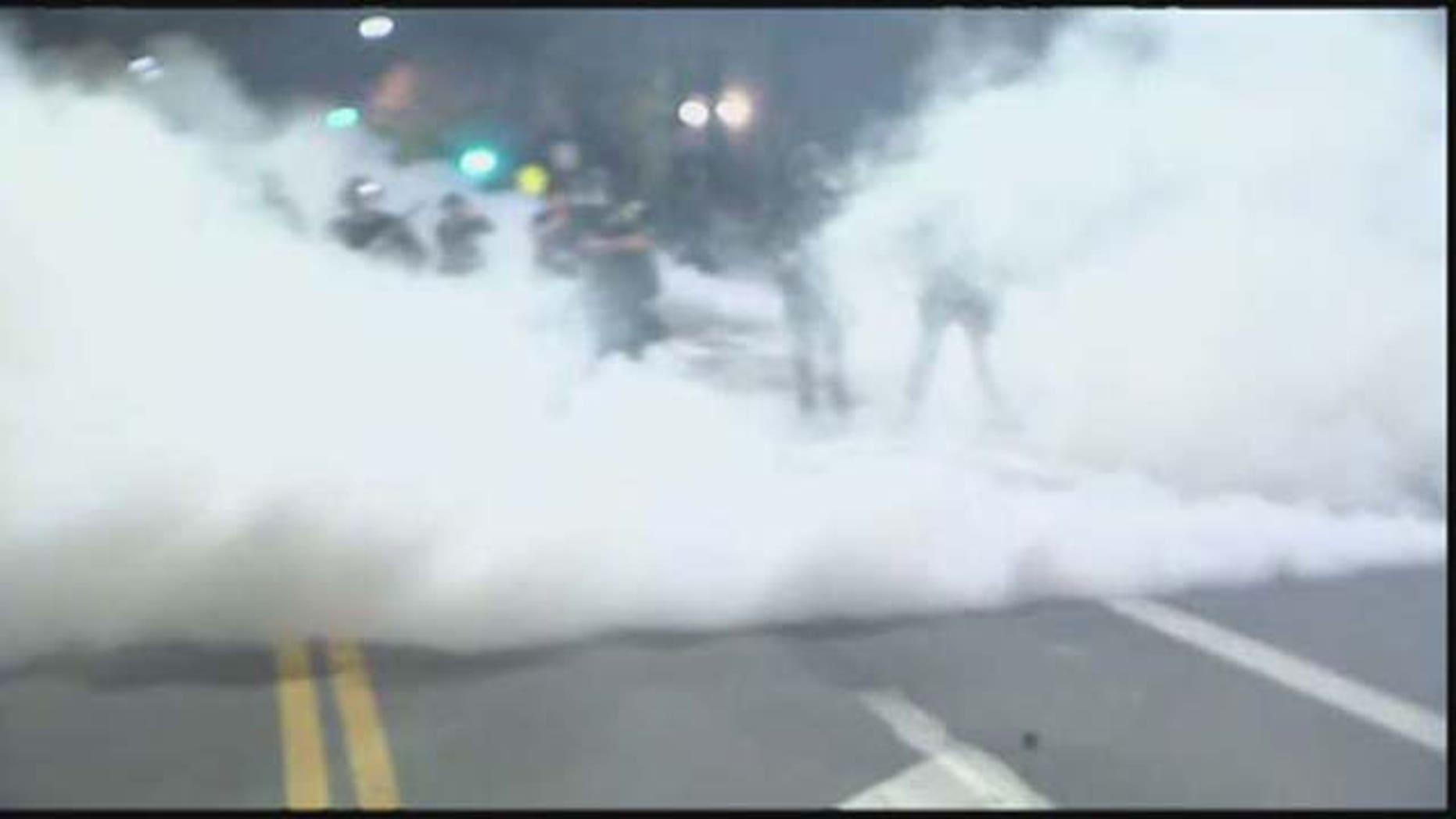 December 6, 2014: Police officers deploy tear gas against violent protesters in Berkeley, Calif. (Courtesy KTVU)