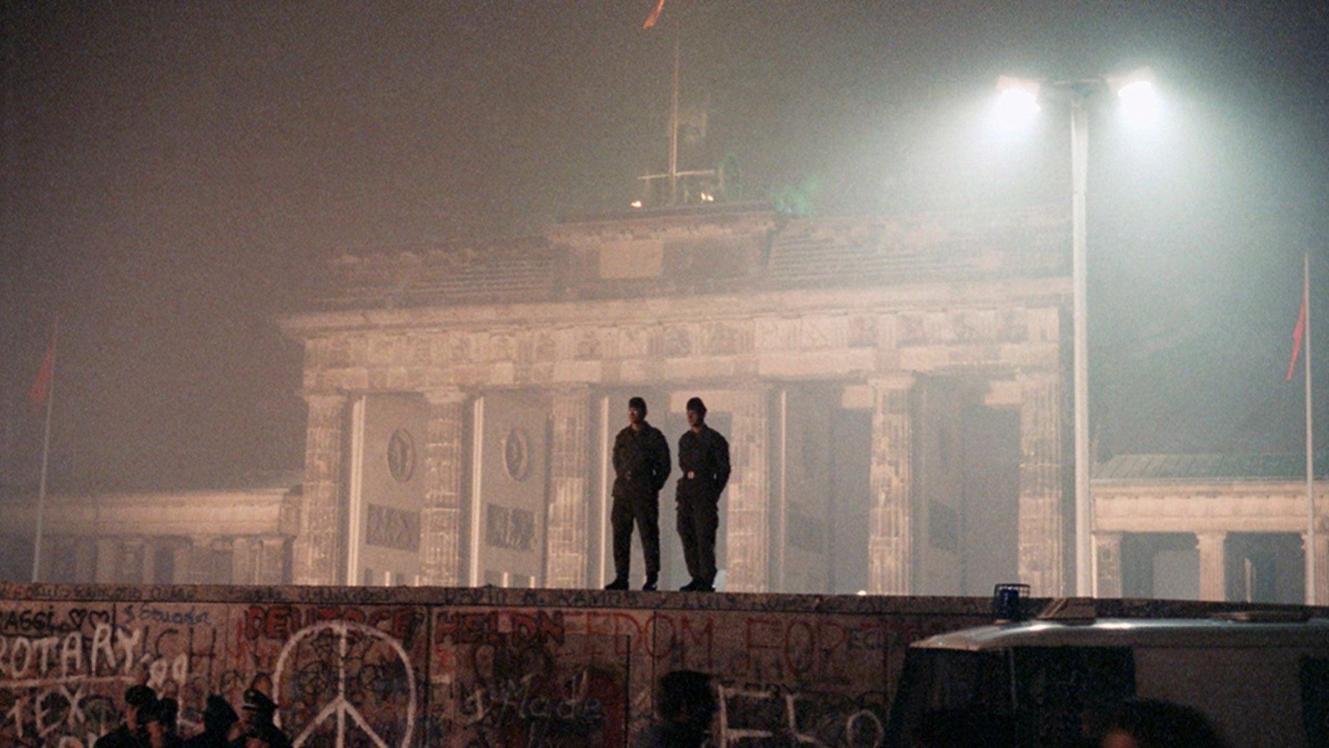 In this November 1989 file photo, two East German border guards patrolled atop the Berlin Wall with the illuminated Brandenburg Gate in the background.