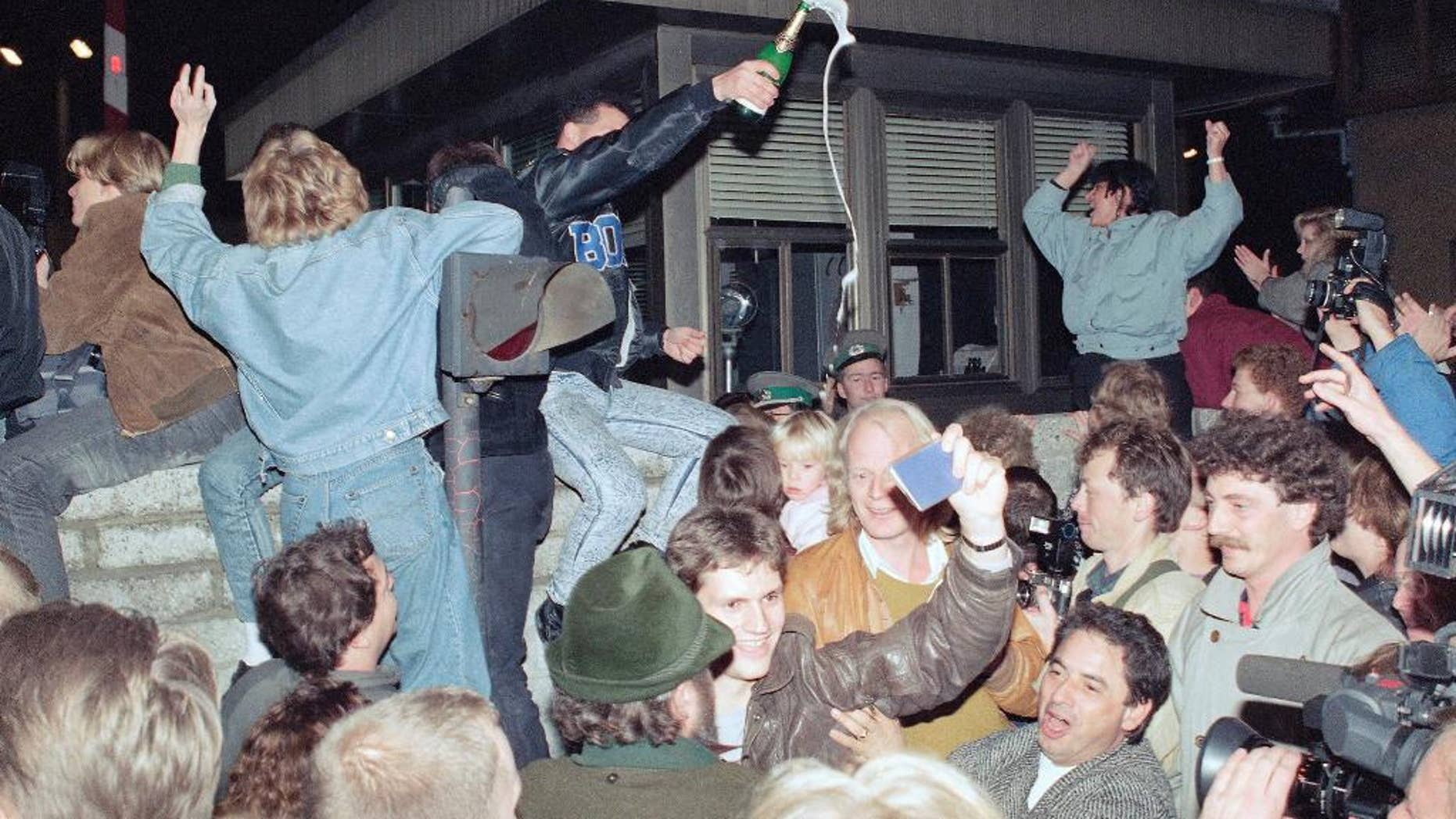 NOV. 10, 1989 - FILE PHOTO - East and West Berliners celebrating in front of a control station on East Berlin territory, during the opening of the borders to the West following the announcement by the East German government that the border to the West would be open. ADVANCE FOR RELEASE SATURDAY, NOVEMBER 8, 2014, AT 12:01 A.M