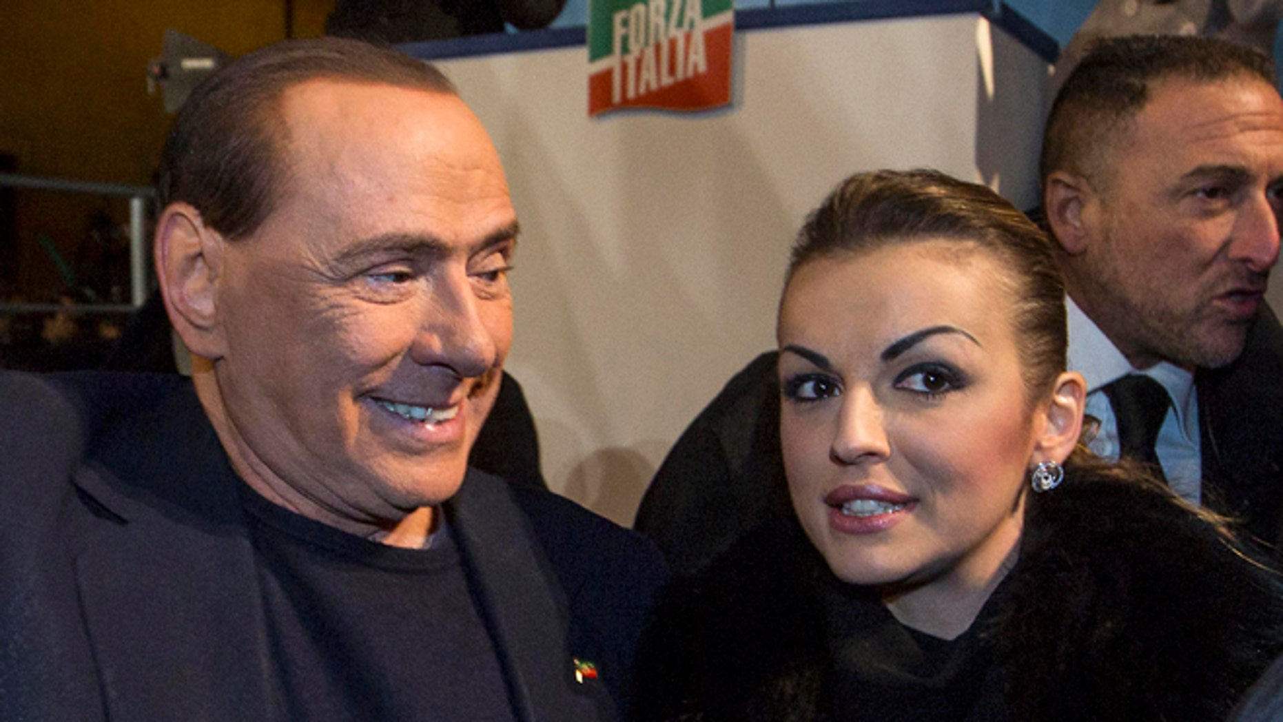 Nov. 27, 2013: Silvio Berlusconi, left, is flanked by his girlfriend Francesca Pascale as he leaves after addressing a rally in Rome.