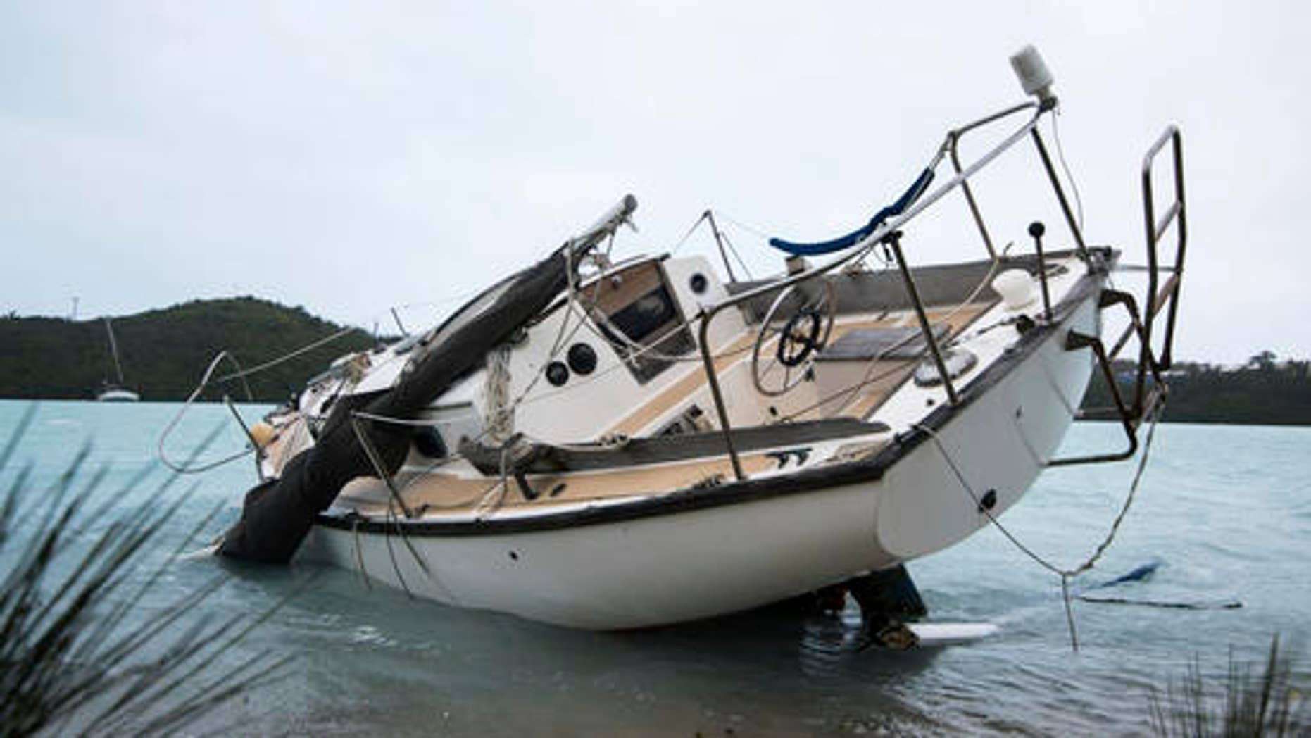 A sailboat lays damaged on the shore of Ferry Reach after breaking free from its mooring after the passing of Hurricane Nicole in St. Georges, Bermuda, Thursday, Oct. 13, 2016. Nicole pummeled the resort island as a Category 3 storm with winds that snapped trees and peeled off roofs before it spun away into open water as a Category 1 storm. (AP Photo/Mark Tatem)
