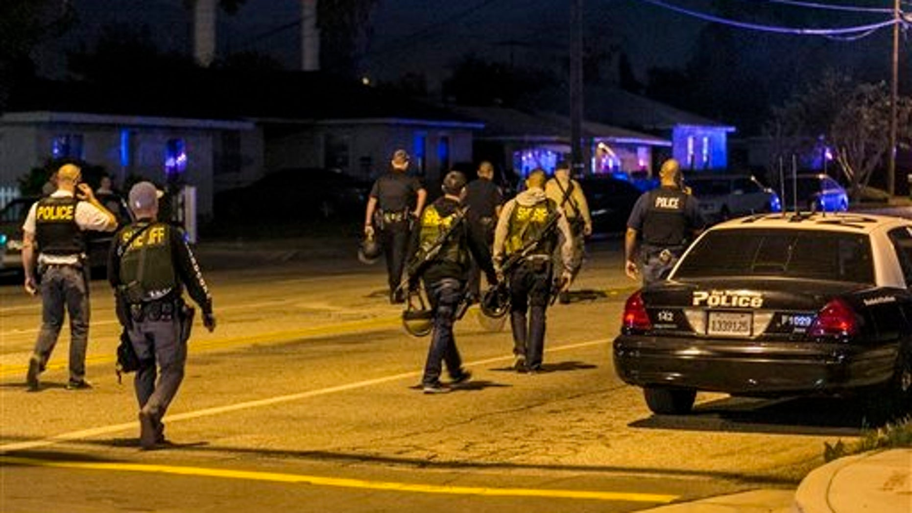 Authorities guard the perimeter near the location of an officer-involved shooting Wednesday, Dec. 2, 2015, in San Bernardino, Calif., following a shooting that killed multiple people at a social services center for the disabled. (AP Photo/Damian Dovarganes)
