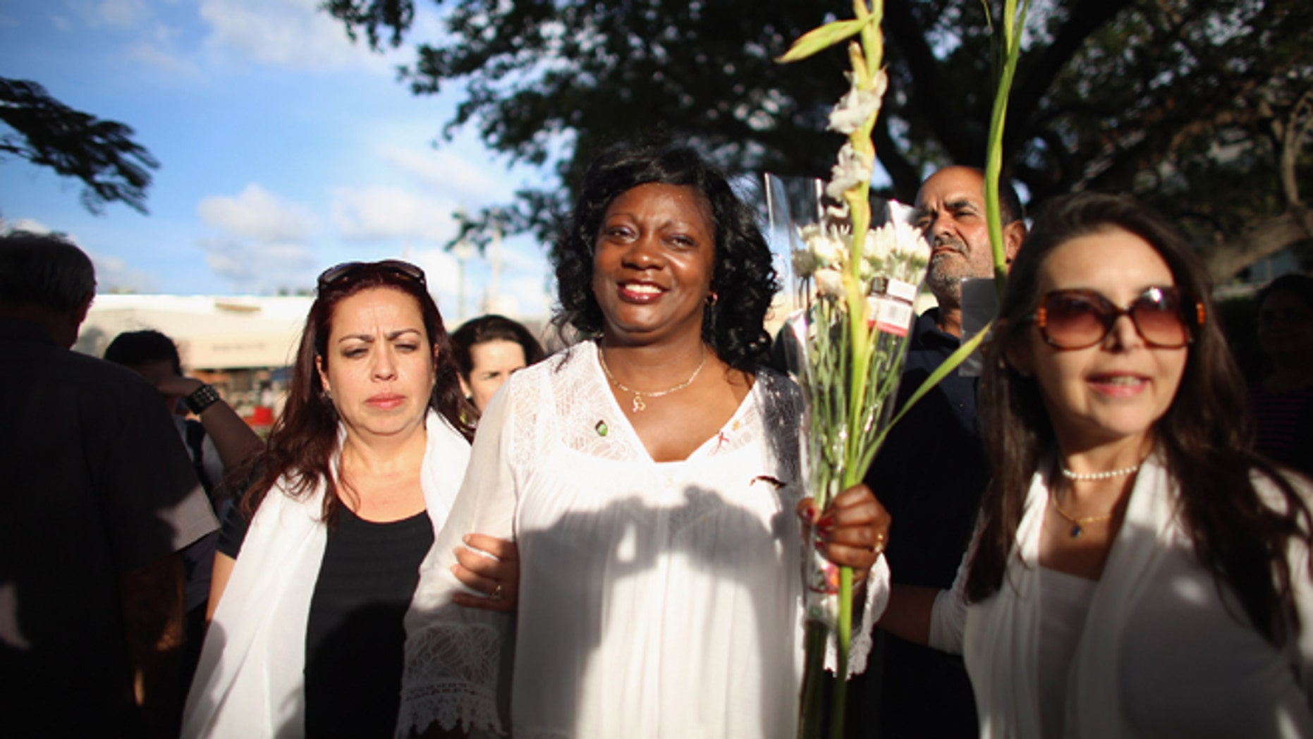 CORAL GABLES, FL - APRIL 27:  Berta Soler, co-founder of the Ladies in White, (C)  and current leader of the Cuban opposition group walks with Janisset Rivero  (L) and others as she visits with Cuban exiles during an event at Merrick Park on April 27, 2013 in Coral Gables, Florida. In Cuba Solerâs group is made up of wives and mothers and was formed in 2003 after the arrests of 75 government opponents.  (Photo by Joe Raedle/Getty Images)