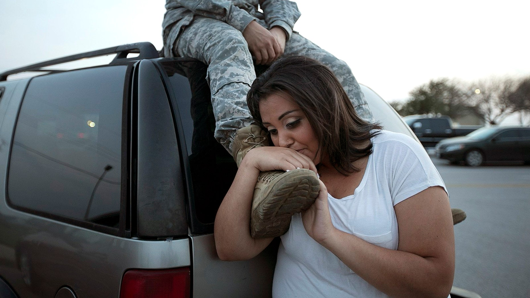 Lucy Hamlin leans on the foot of her husband, Spc. Timothy Hamlin, after a gunman opened fire at Fort Hood, Texas, before committing suicide, in 2014.