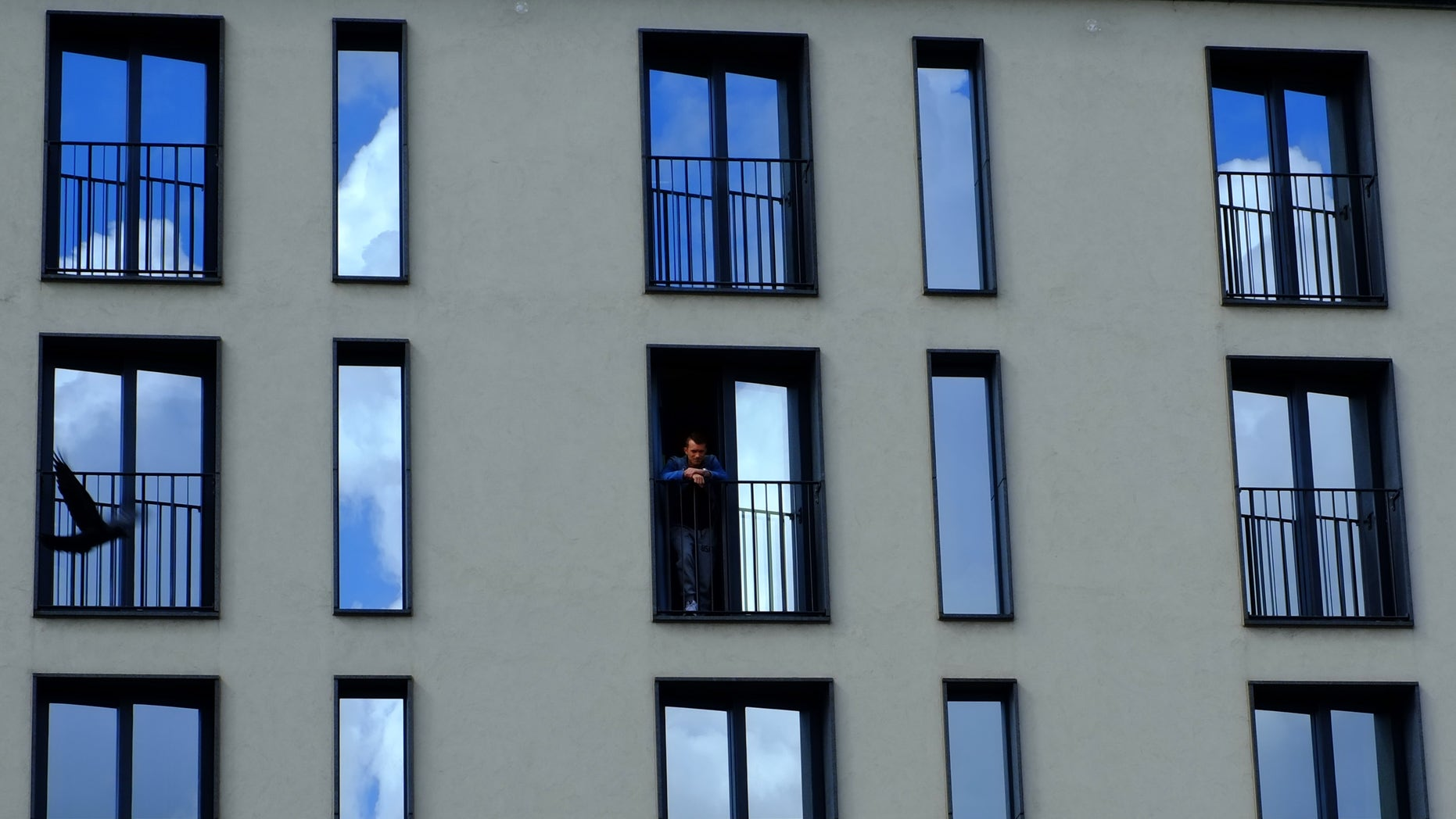 A man stands on a balcony of a hotel, as a pigeon, flies by, in central Gothenburg, Sweden, Thursday, Aug. 14, 2014. (AP Photo/Petros Karadjias)