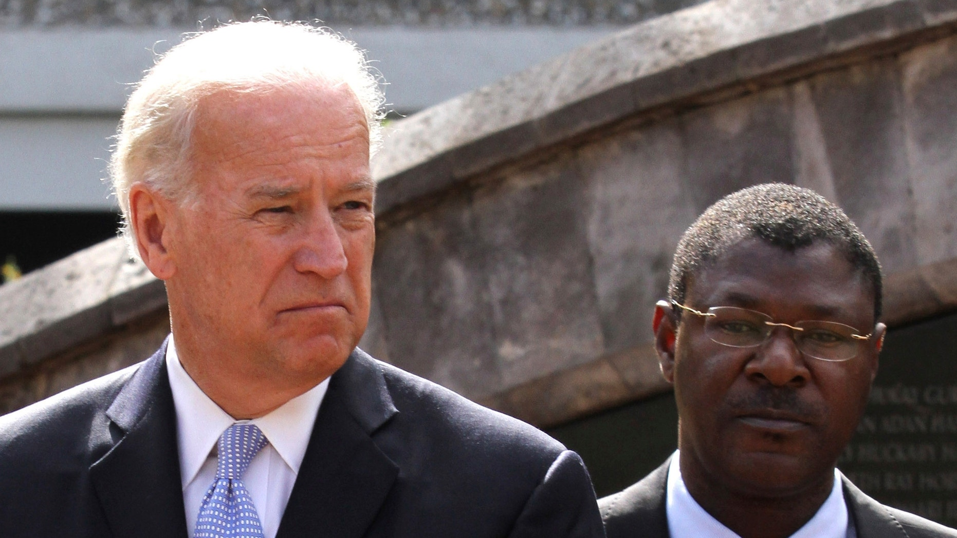 Vice President Biden and Kenyan Foreign Affairs Minister Wetangula look on after laying a wreath at the site of the former U.S. Embassy in Nairobi. While in Kenya, Biden expressed support for the proposed new constitution, which Kenya approved on Aug. 4. (Reuters)
