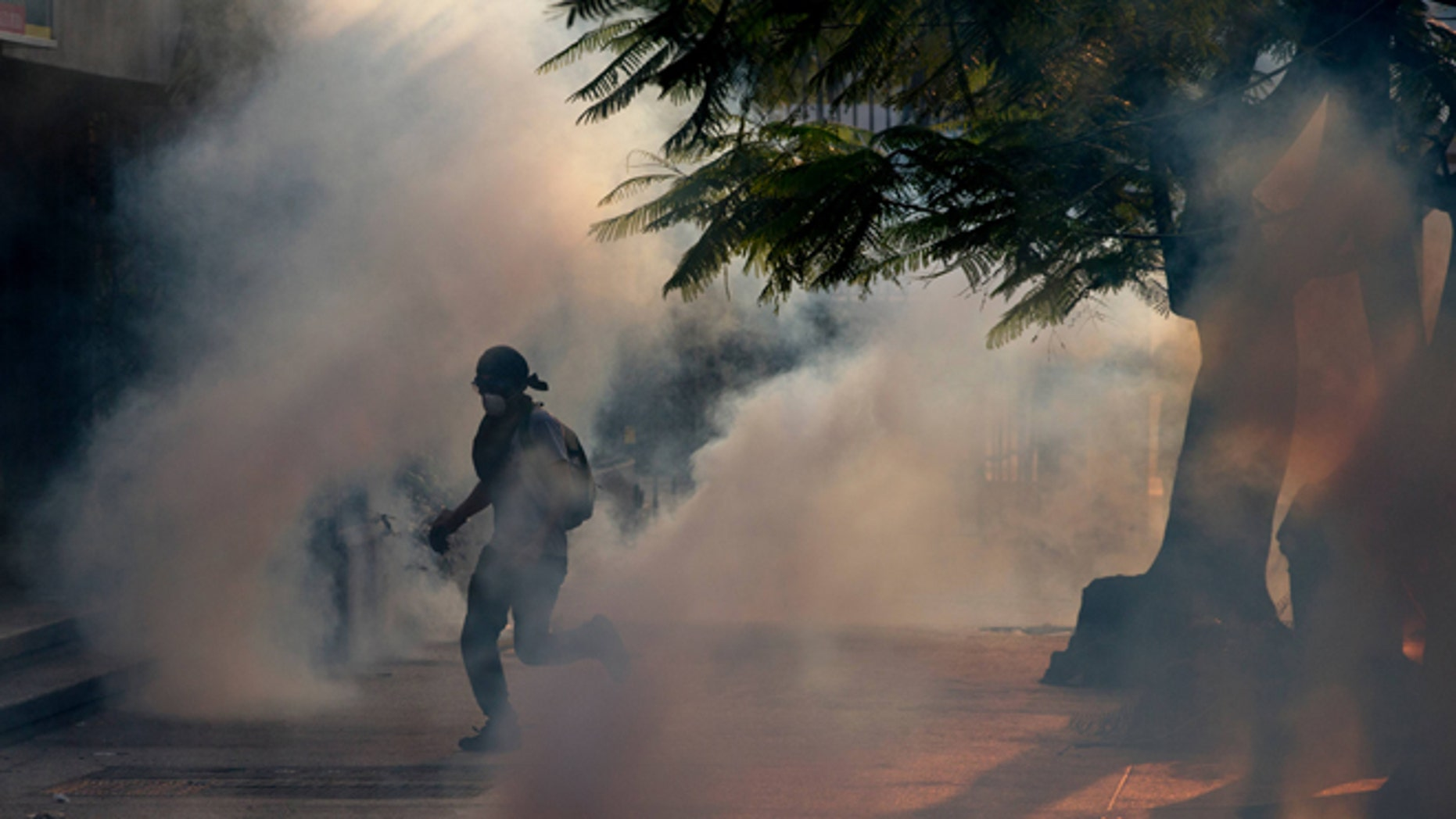 A demonstrator take cover from tear gas fired by Bolivarian National police during clashes with anti-government protesters in Caracas,Venezuela, Saturday, March 8, 2014. The Venezuelan government and opposition appear to have reached a stalemate, in which street protests continue almost daily while the opposition sits out a peace process it calls farcical. (AP Photo/Fernando Llano)