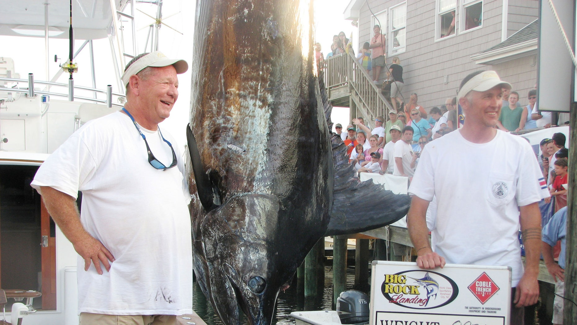 June 14, 2012: Citation angler Andy Thomossan, left, and Eric Holmes stand next to their 883-pound blue marlin, which broke the record for the biggest blue marlin in the 52-year history of the Big Rock Blue Marlin Tournament in Morehead City, N.C.