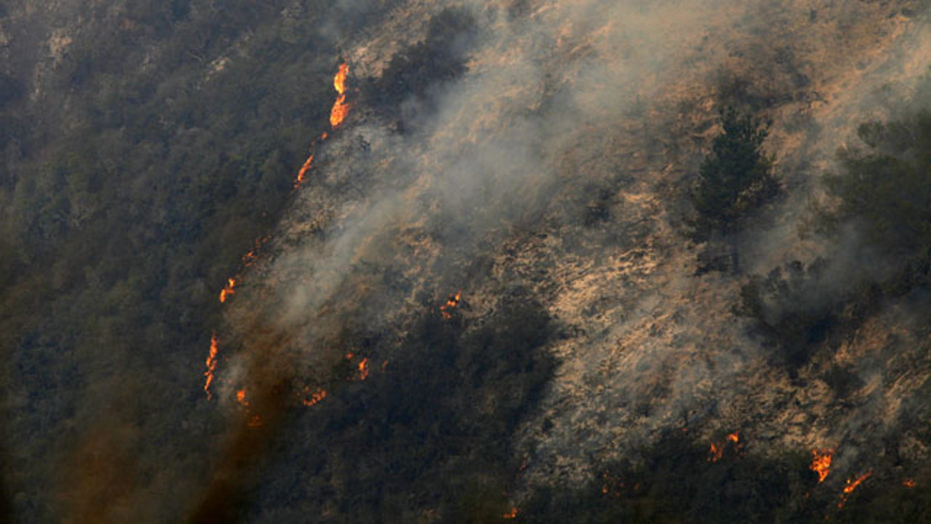 December 17, 2013: Flames creep down a hillside as firefighters battle a fire in the Pfeiffer Ridge area of Big Sur, Calif. Firefighters are making gains against the unusual fall wildfire that has destroyed 15 homes and forced about 100 people to flee the forested mountains of California's scenic Big Sur region overlooking the Pacific. (AP Photo)