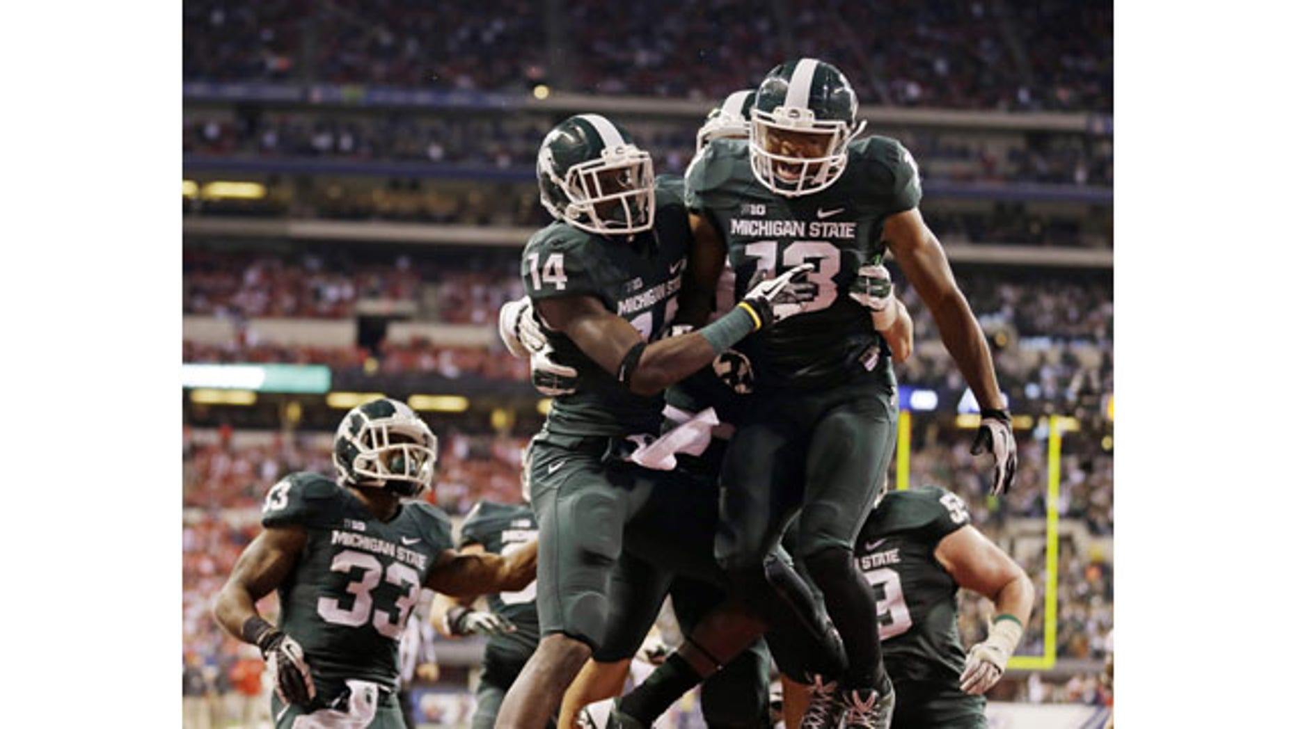 December 7, 2013: Michigan State's Tony Lippett (14) celebrates with Bennie Fowler (13) after a 33-yard touchdown reception by Lippett during the first half of the Big Ten championship game in Indianapolis. (AP Photo/Michael Conroy)