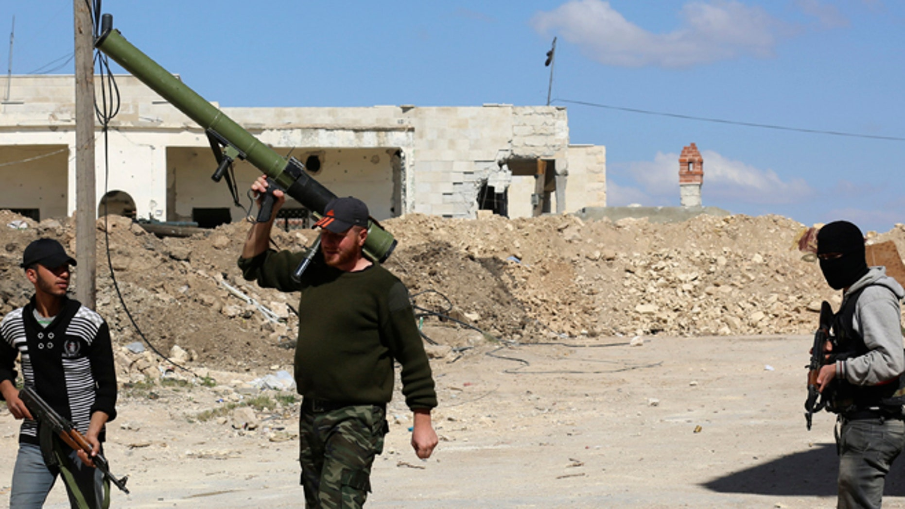 April 9, 2014: Rebel fighters carry their weapons as they walk along a street in the town of Morek in Hama province.