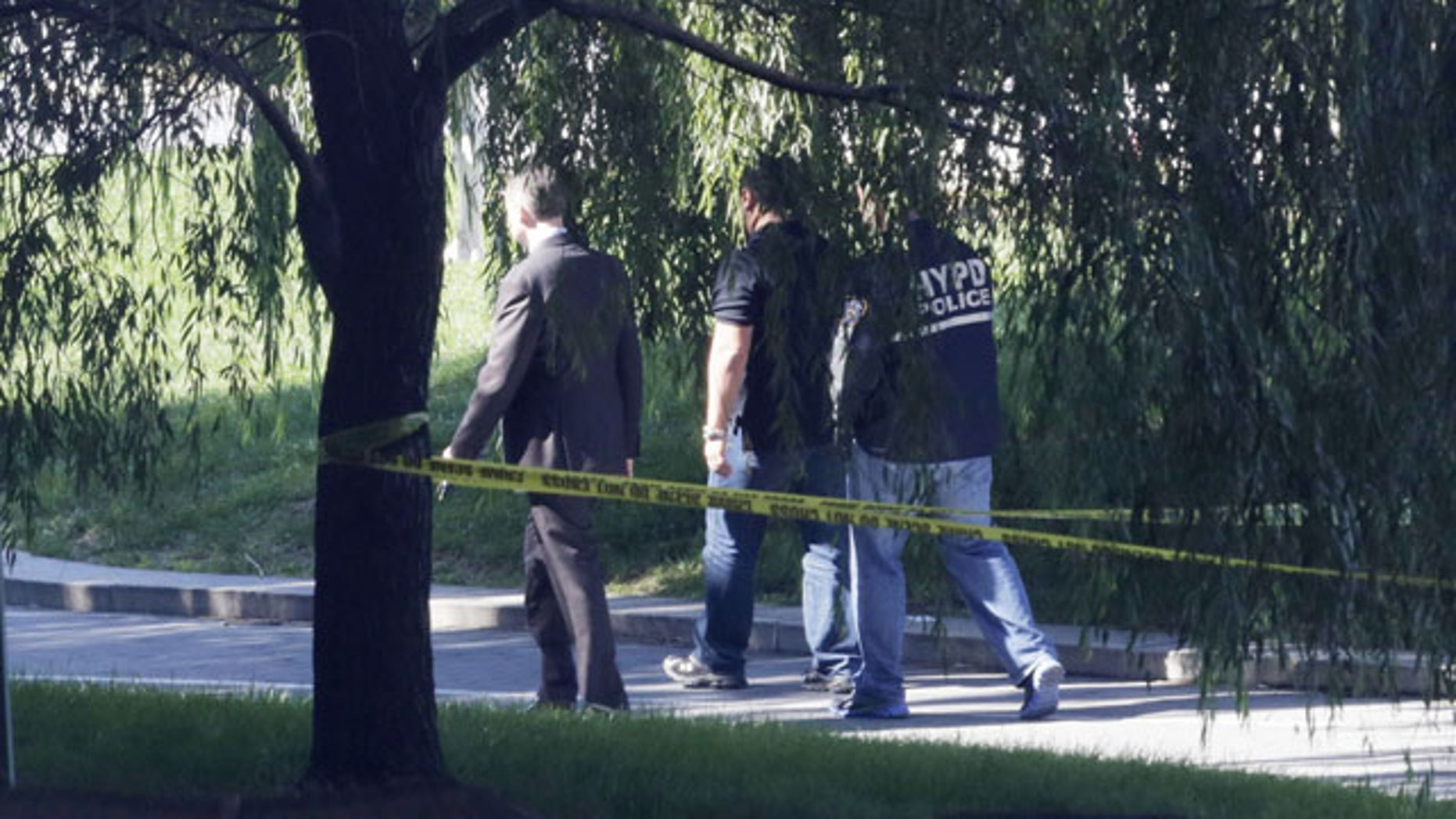 October 1, 2013: Crime scene investigators walk along a path in New York's Riverside Park South where a man earlier went on a rampage stabbing five people Tuesday, including a toddler. (AP Photo)