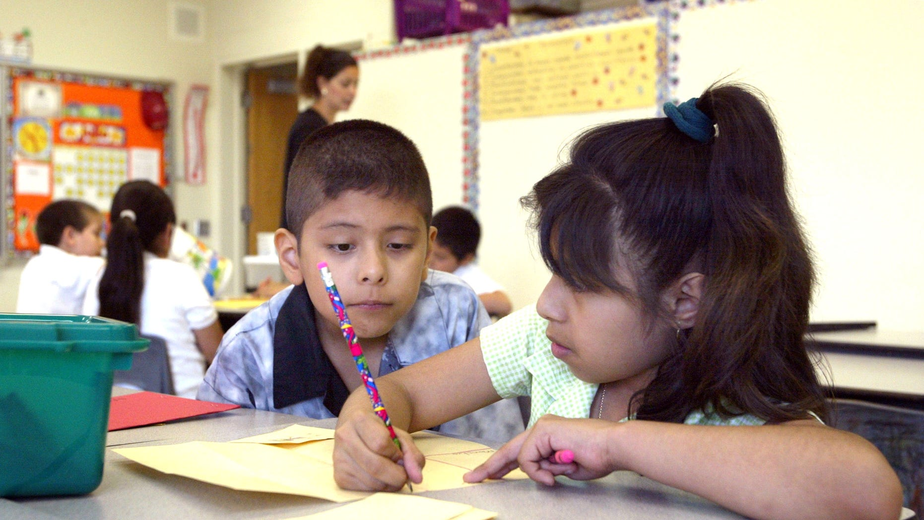 CHICAGO, IL - JULY 2:  Students work together in teacher Daisy Moran's second-grade bilingual class during summer school at Mozart School July 2, 2003 in Chicago, Illinois. A record number of students are expected at summer school due to a strong showing for a new voluntary program for mid-tier students and strict application of non-ITBS (Iowa Tests of Basic Skills) test promotion standards.  (Photo by Tim Boyle/Getty Images)
